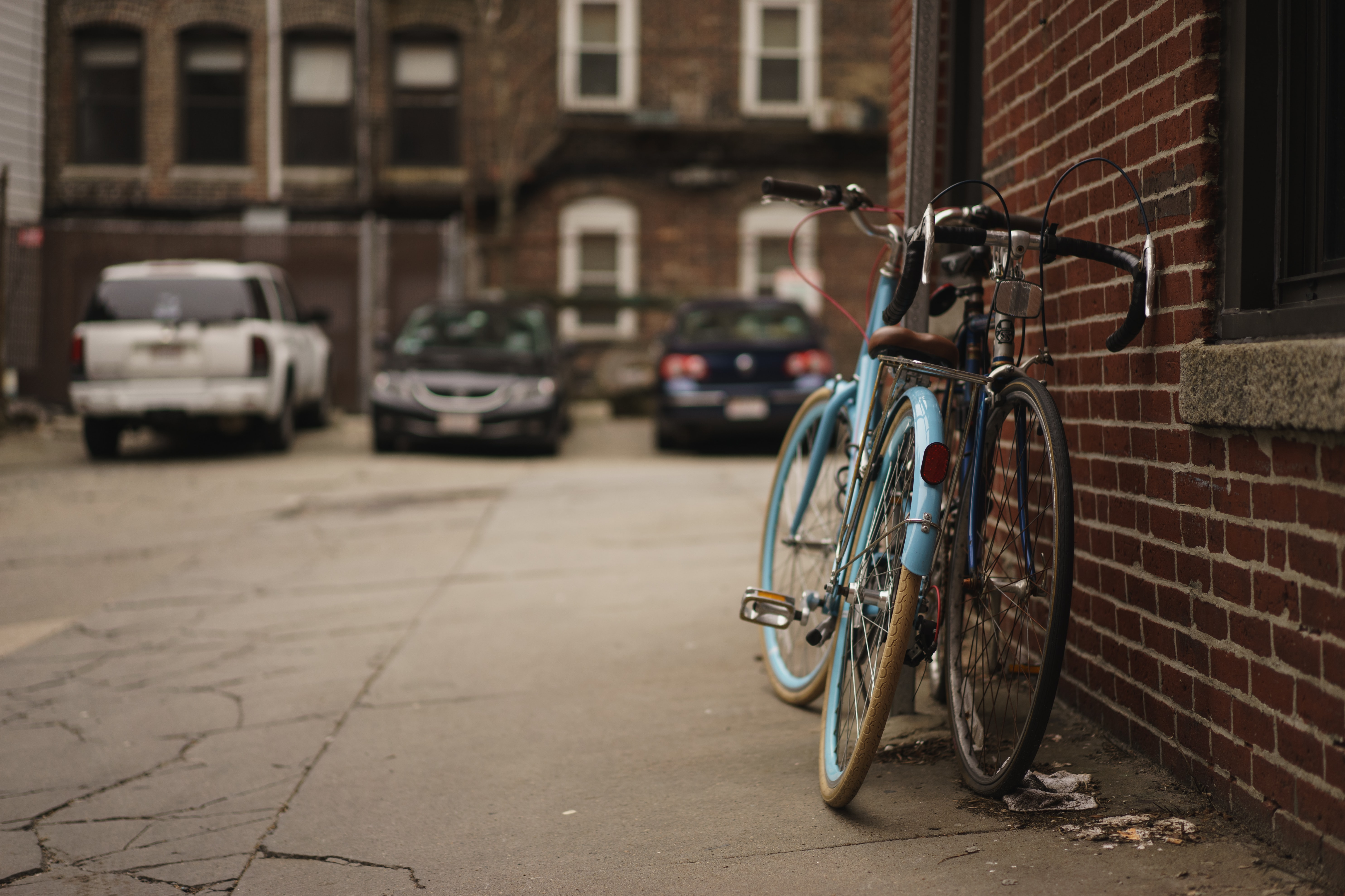 Two bicycles leaning against red brick wall in urban car park, 23 Foster St