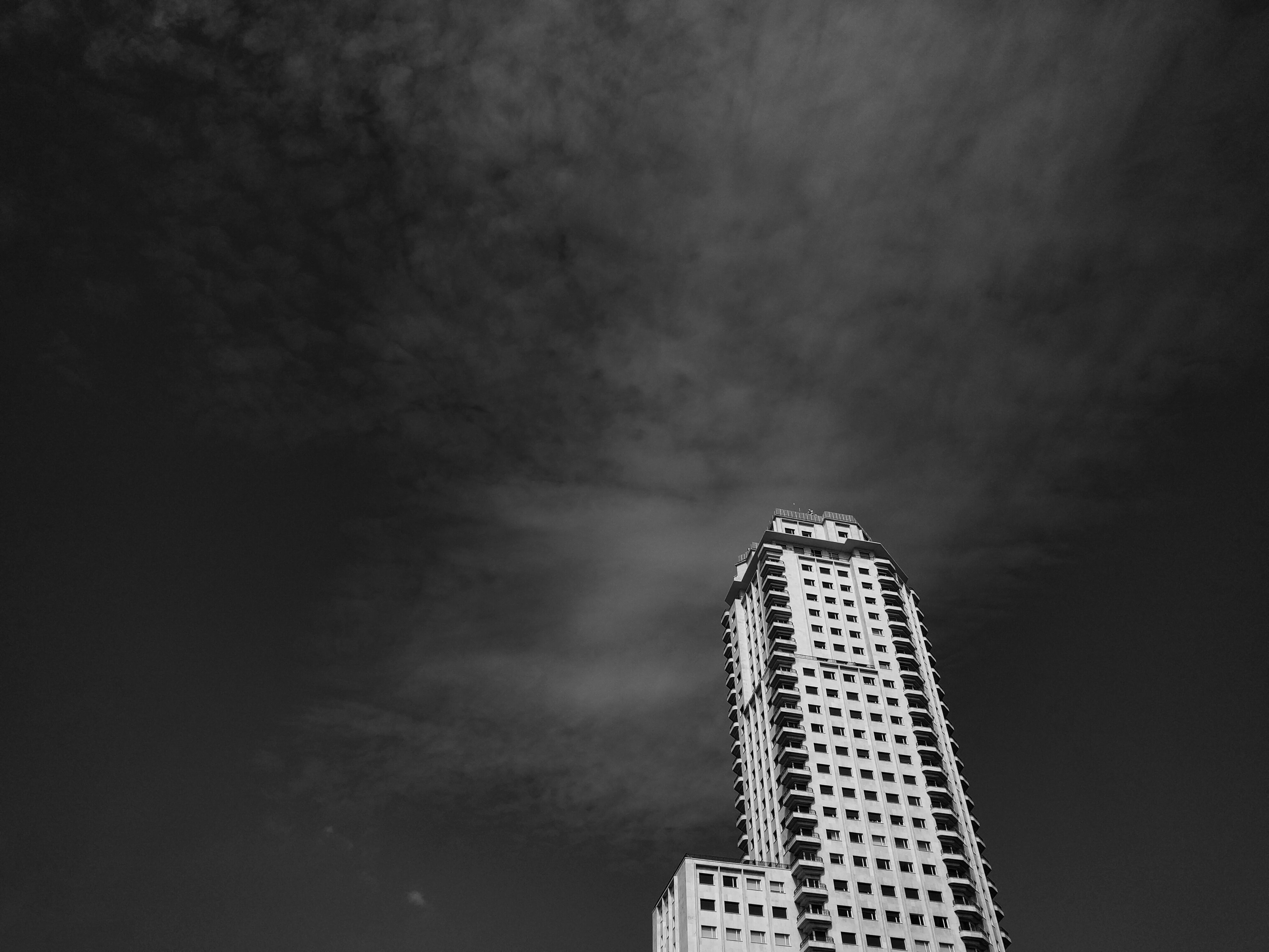 Black and white view of the Torre de Madrid with a dark sky