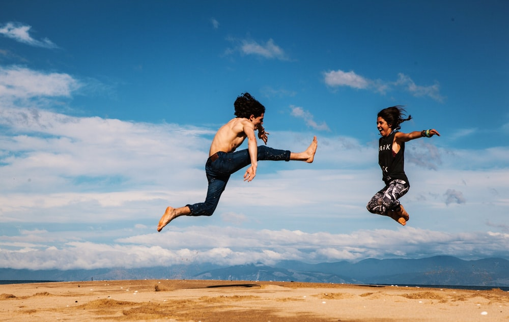 A couple jumping really high in the sky kicking their feet up at Abel Tasman National Park