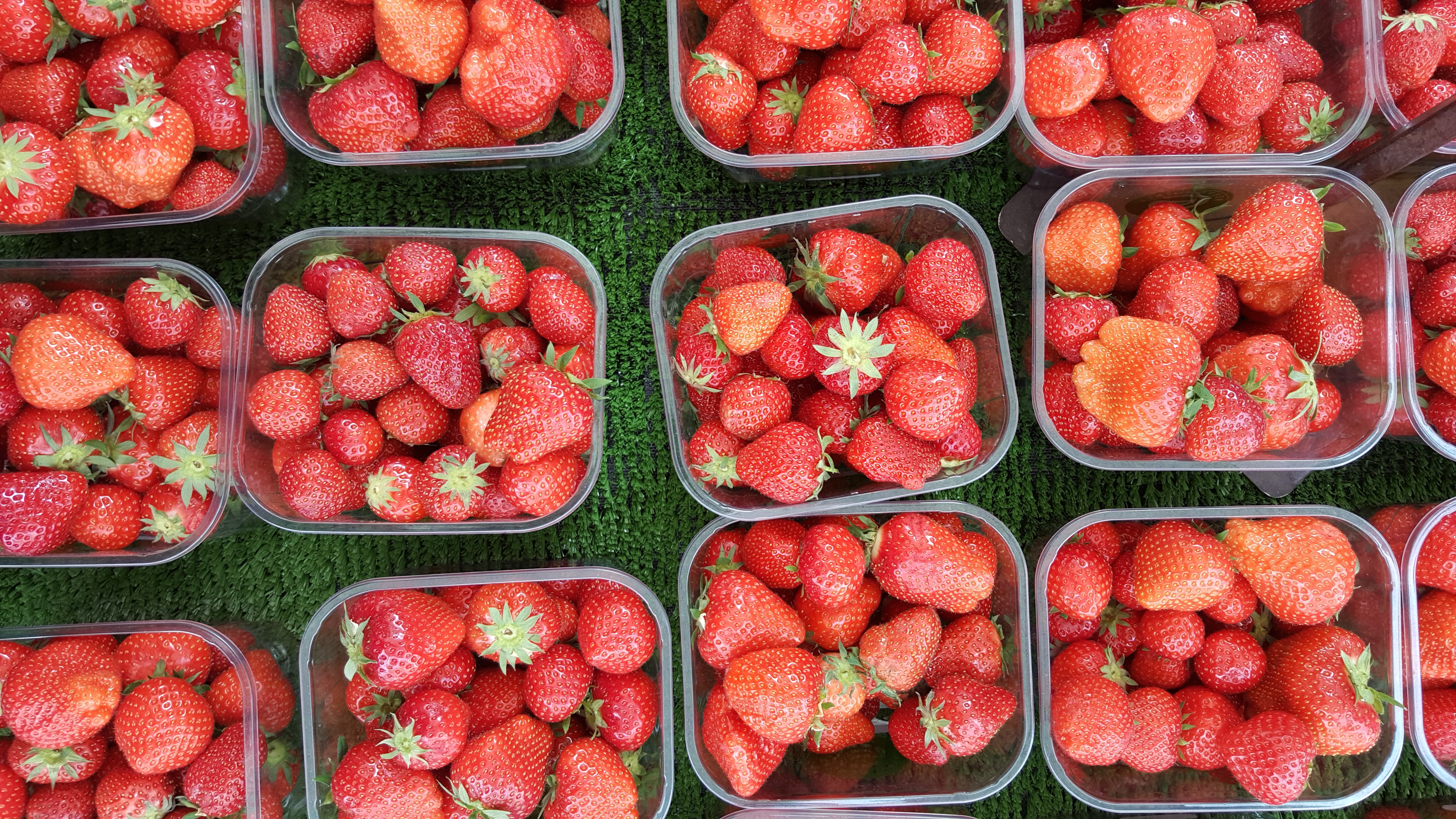 Baskets of fresh red strawberries at a produce market