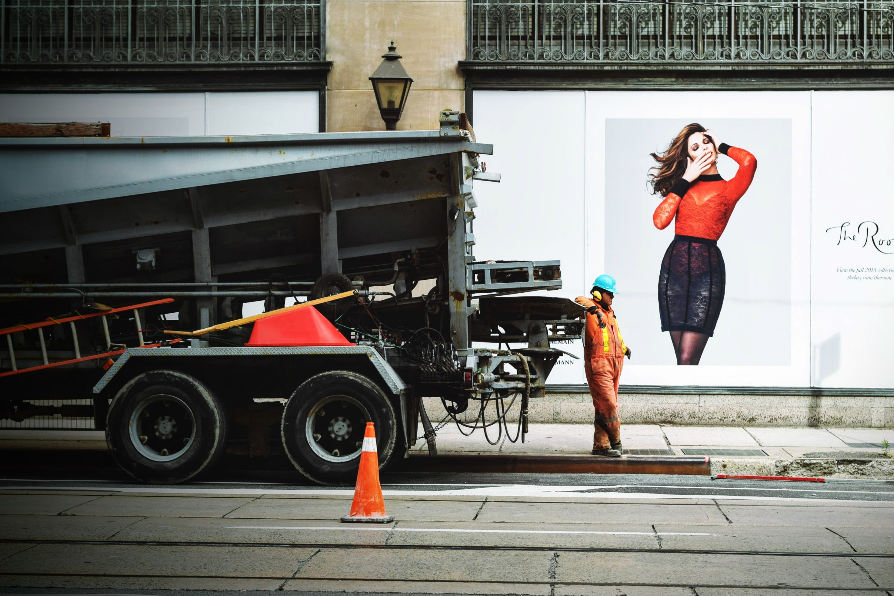 A construction worker stands alongside a truck with a wall of advertisements behind him