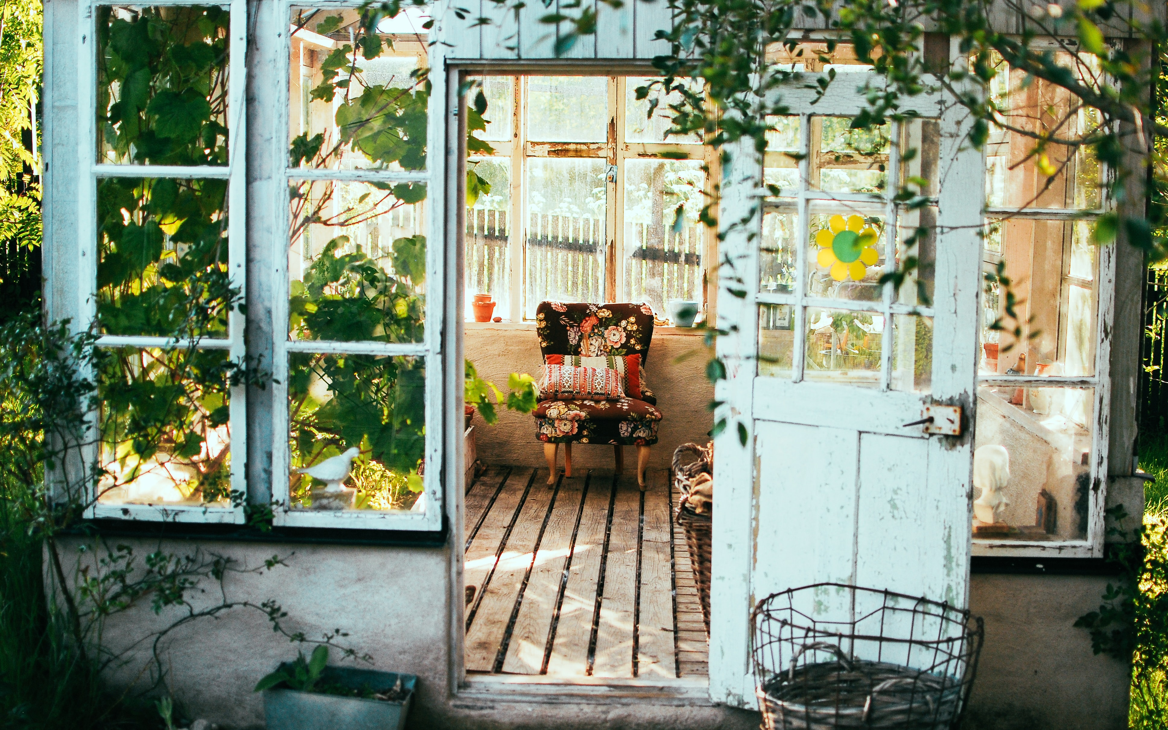 Exquisite greenhouse surrounded by sunflowers  with colorful folding chair inside