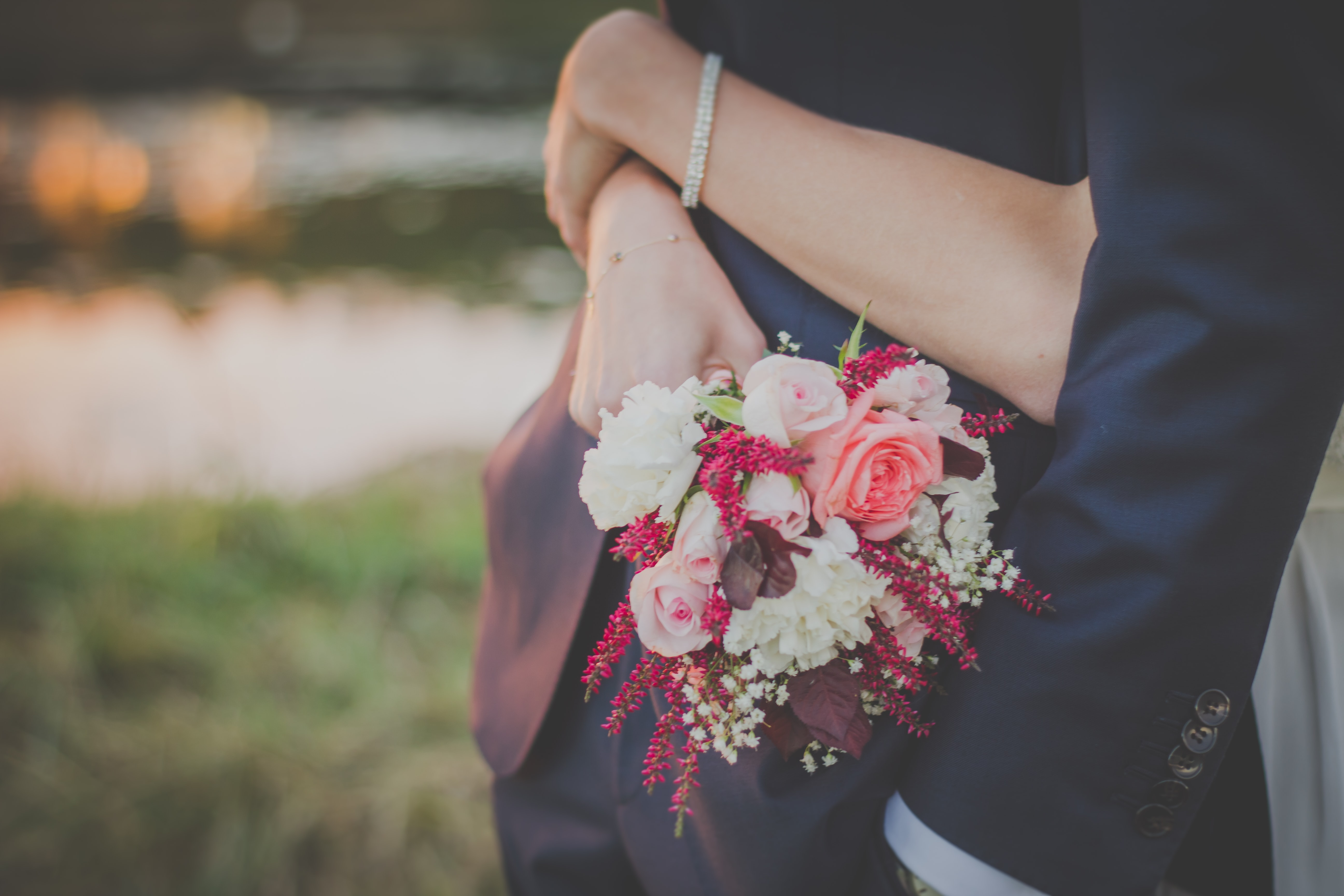Bride holds a wedding bouquet of roses while wrapping arms around her groom