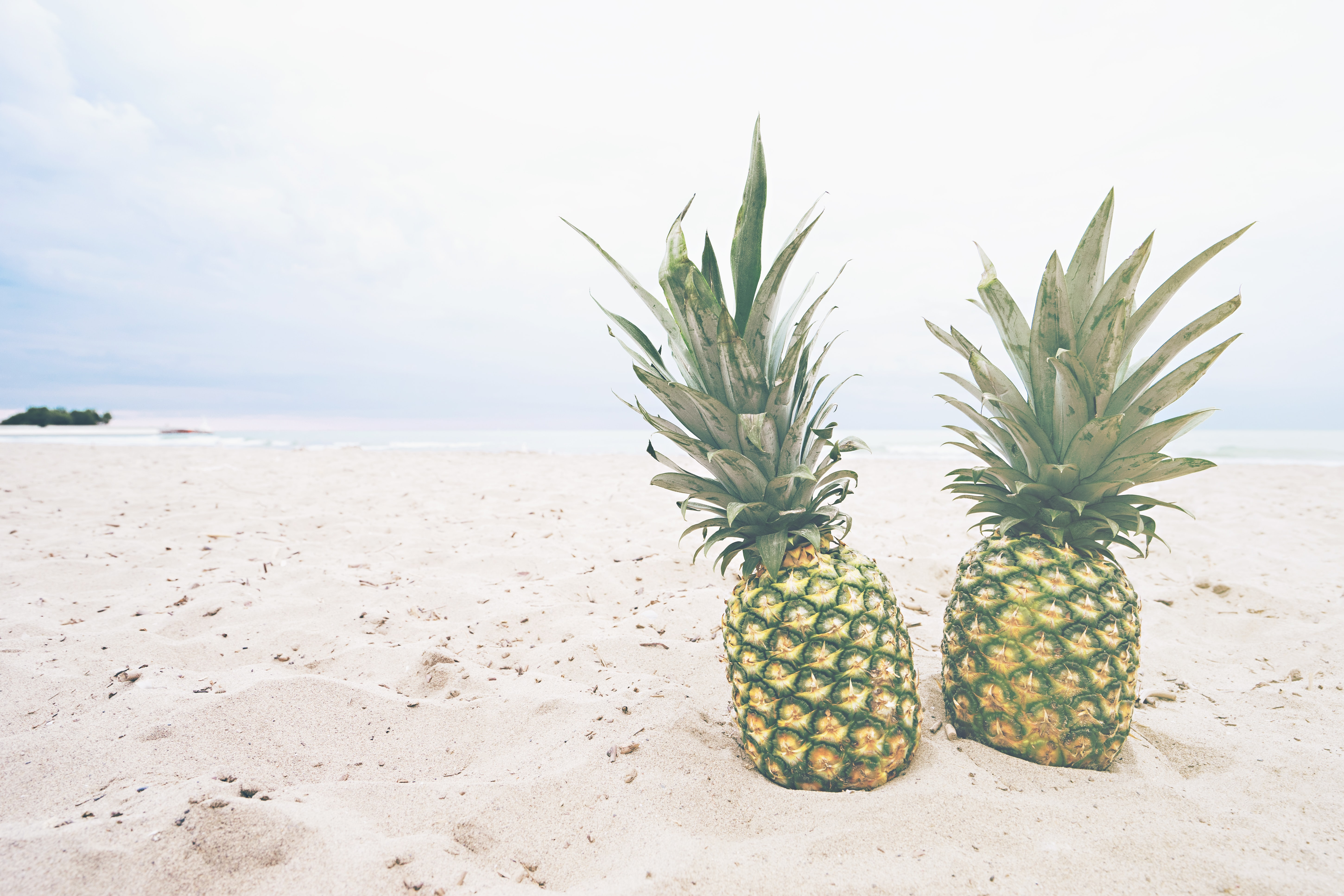 A couple of pineapples side by side on the beach.