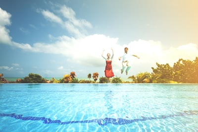 man and woman jumping onto pool cancun teams background