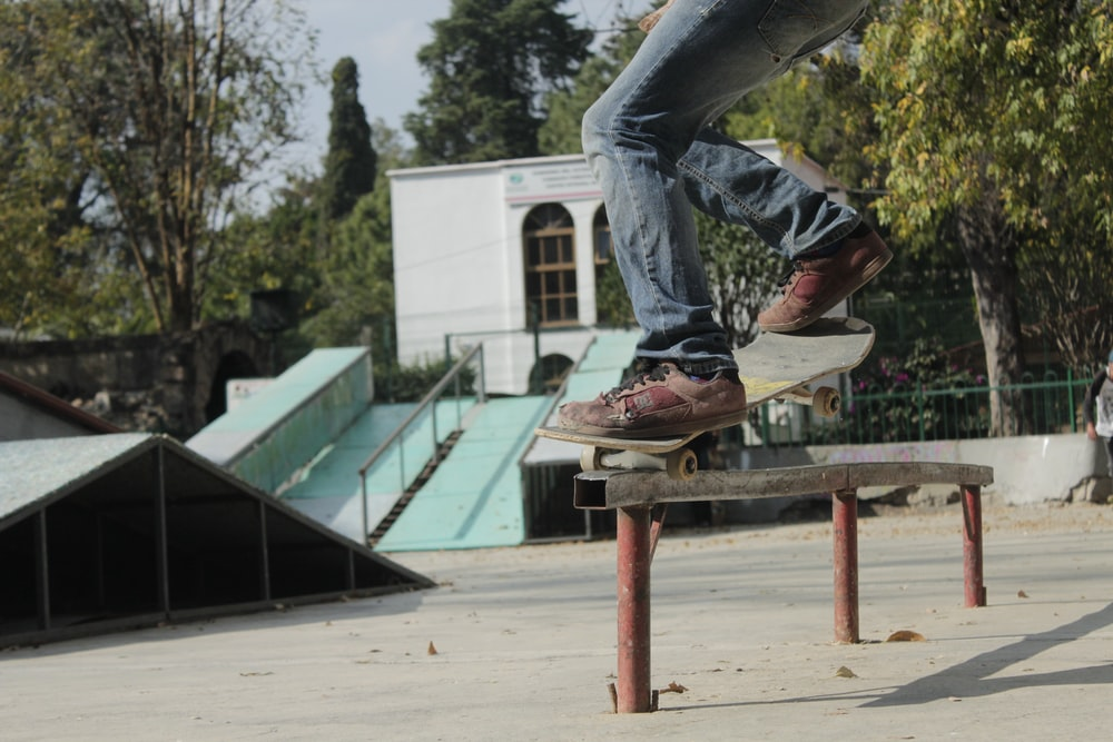 person skating on rail during daytime