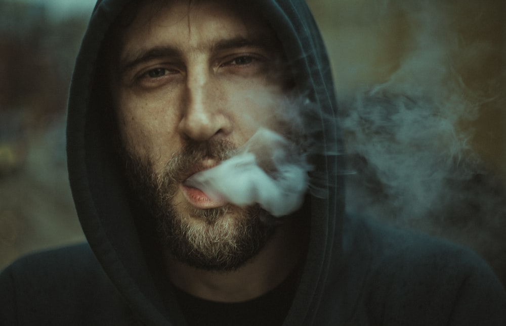 Man in a hoodie exhaling smoke from his mouth
