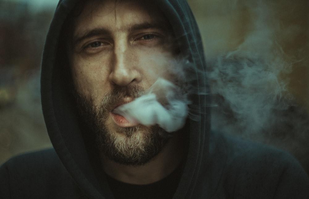 man wearing black pullover hoodie blowing white smoke