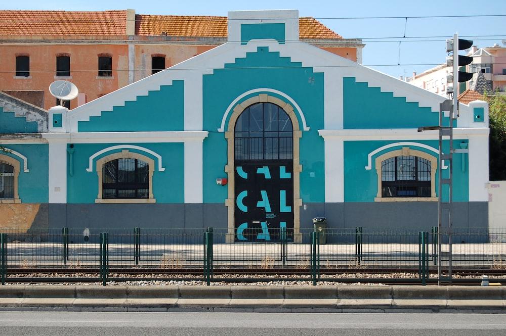 teal house near railway