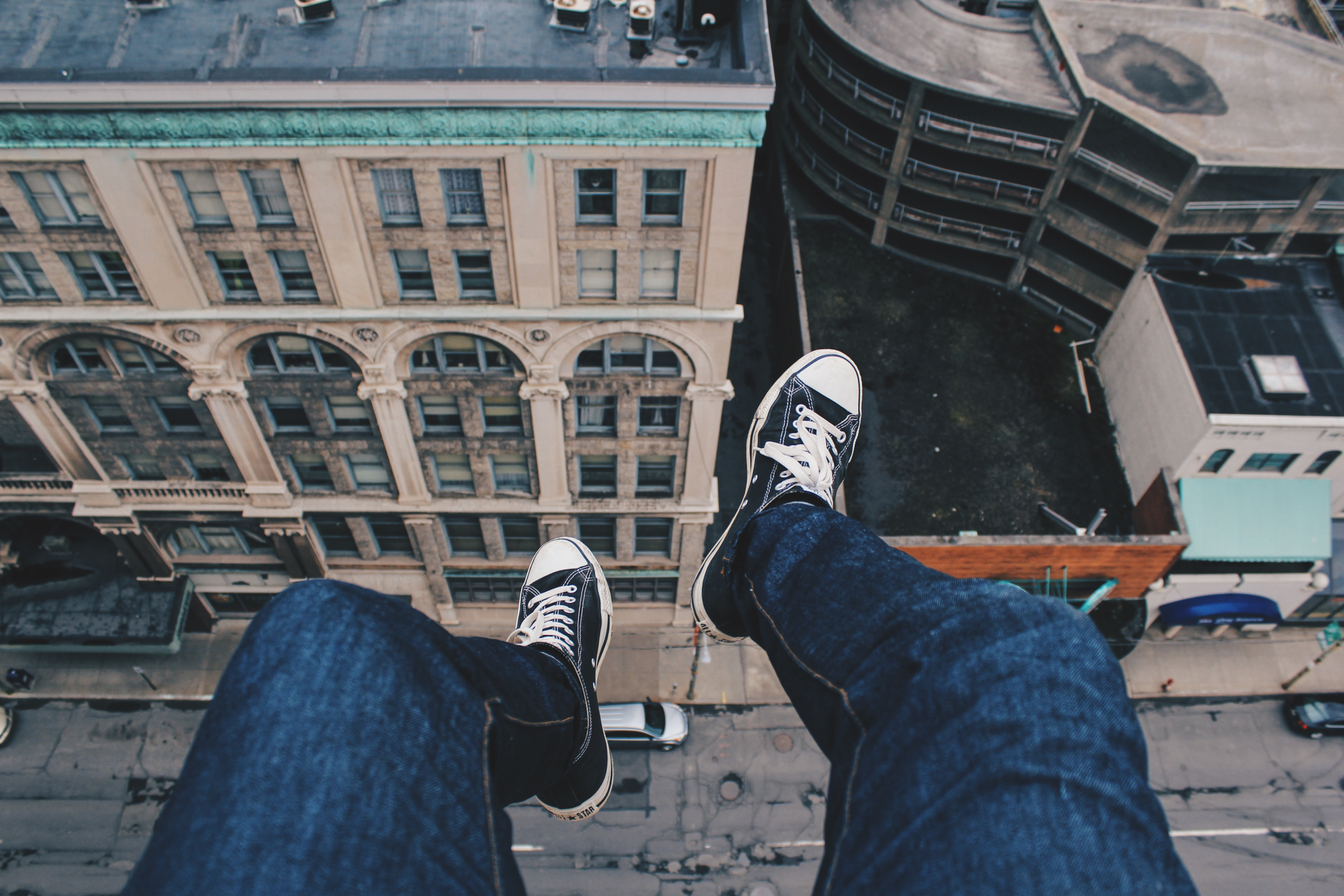 Person wearing Converse sneakers dangling their feet off building's rooftop ledge above the traffic