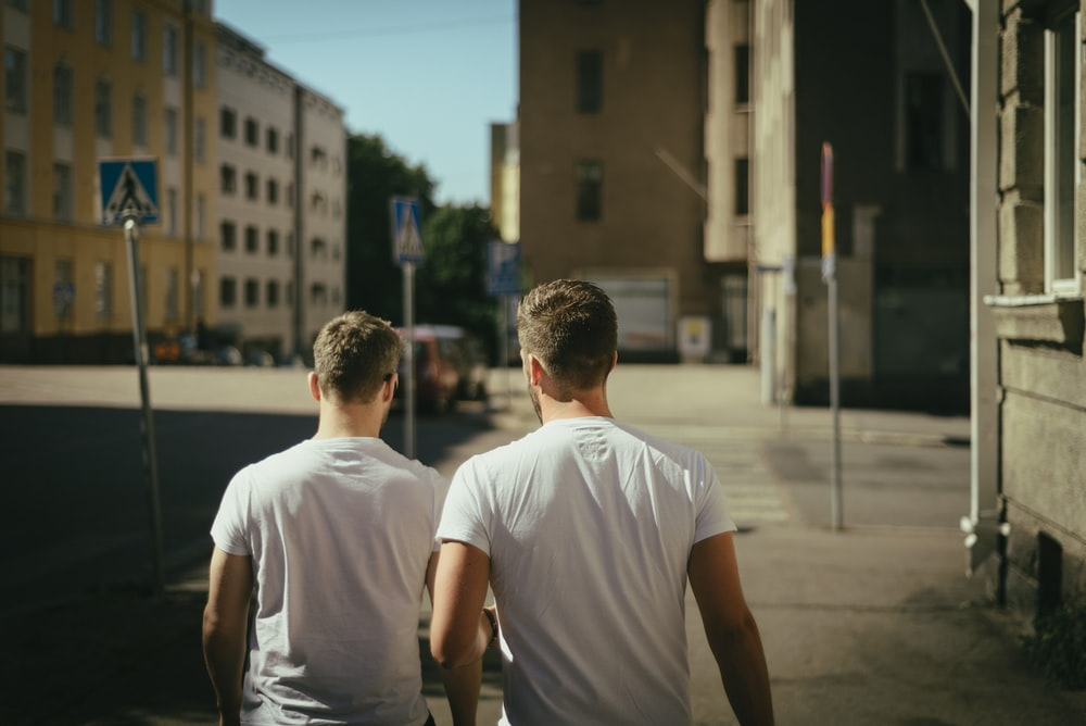 Two men in white t-shirts walk away down a city street
