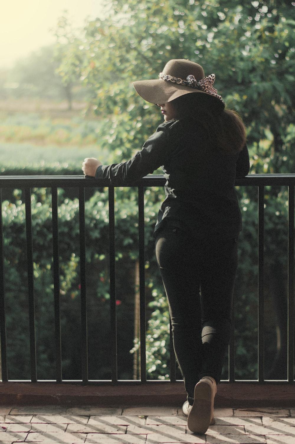 woman in black jacket and black pants wearing brown hat standing beside black metal fence during