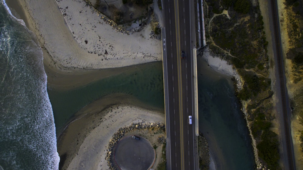 aerial photography of black and white vehicles on road between body of water and