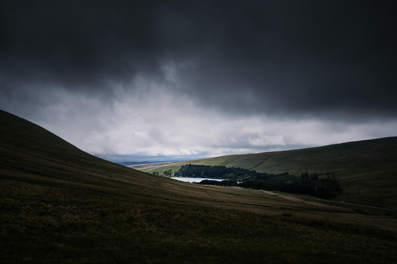 brown mountain under cumulos clouds