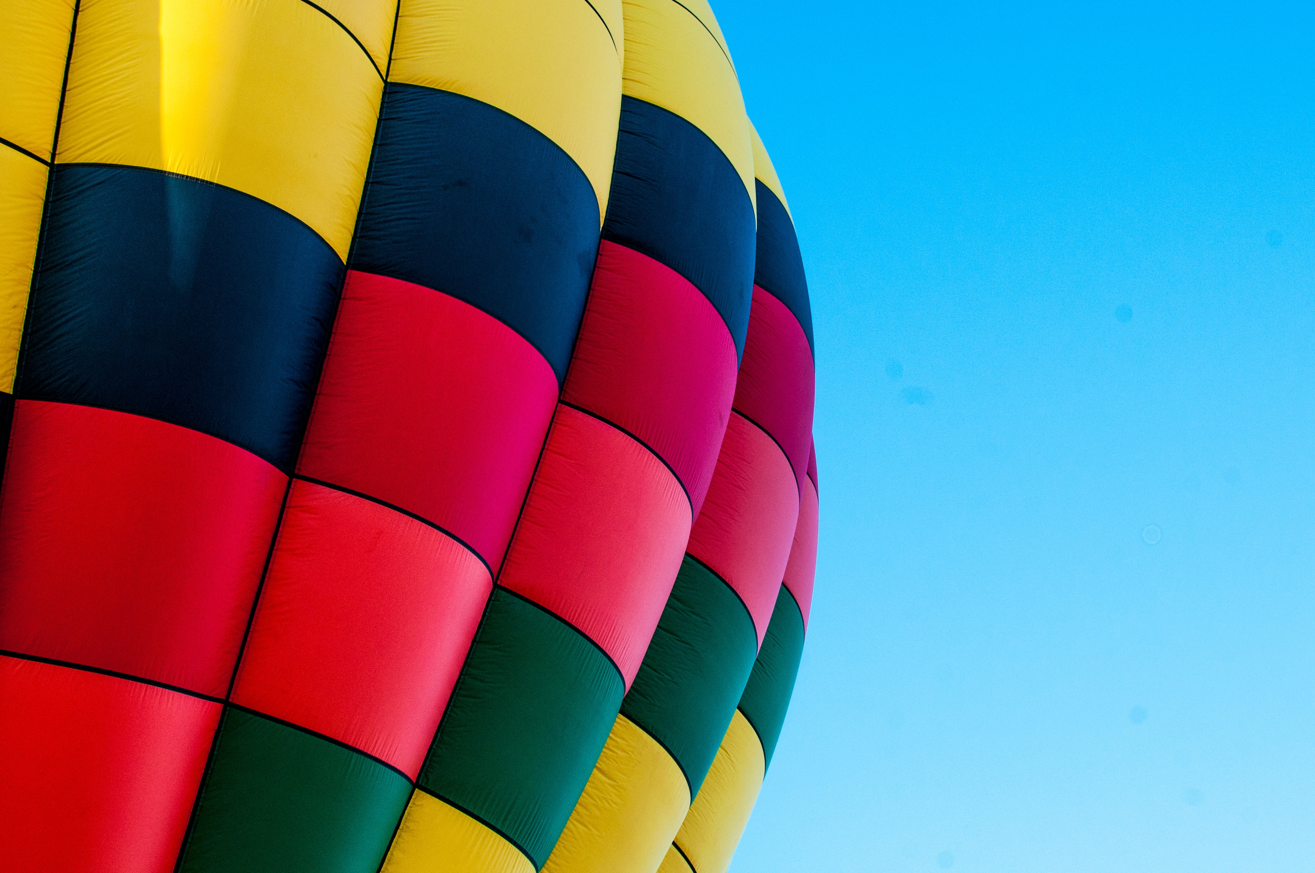 The colorful surface of a hot air balloon against a blue sky