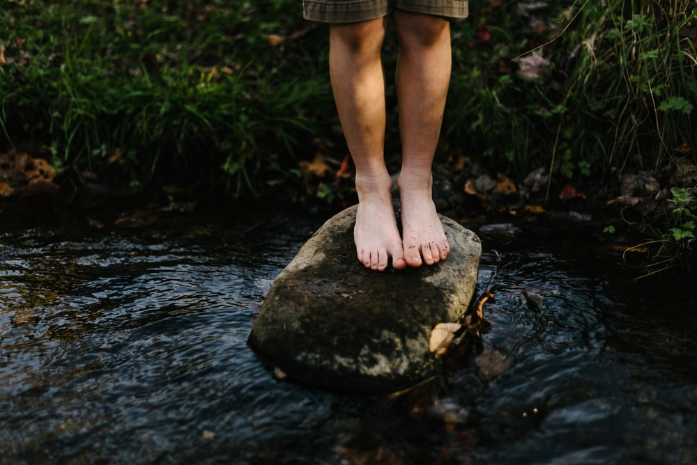 person standing on stone at center of body of water