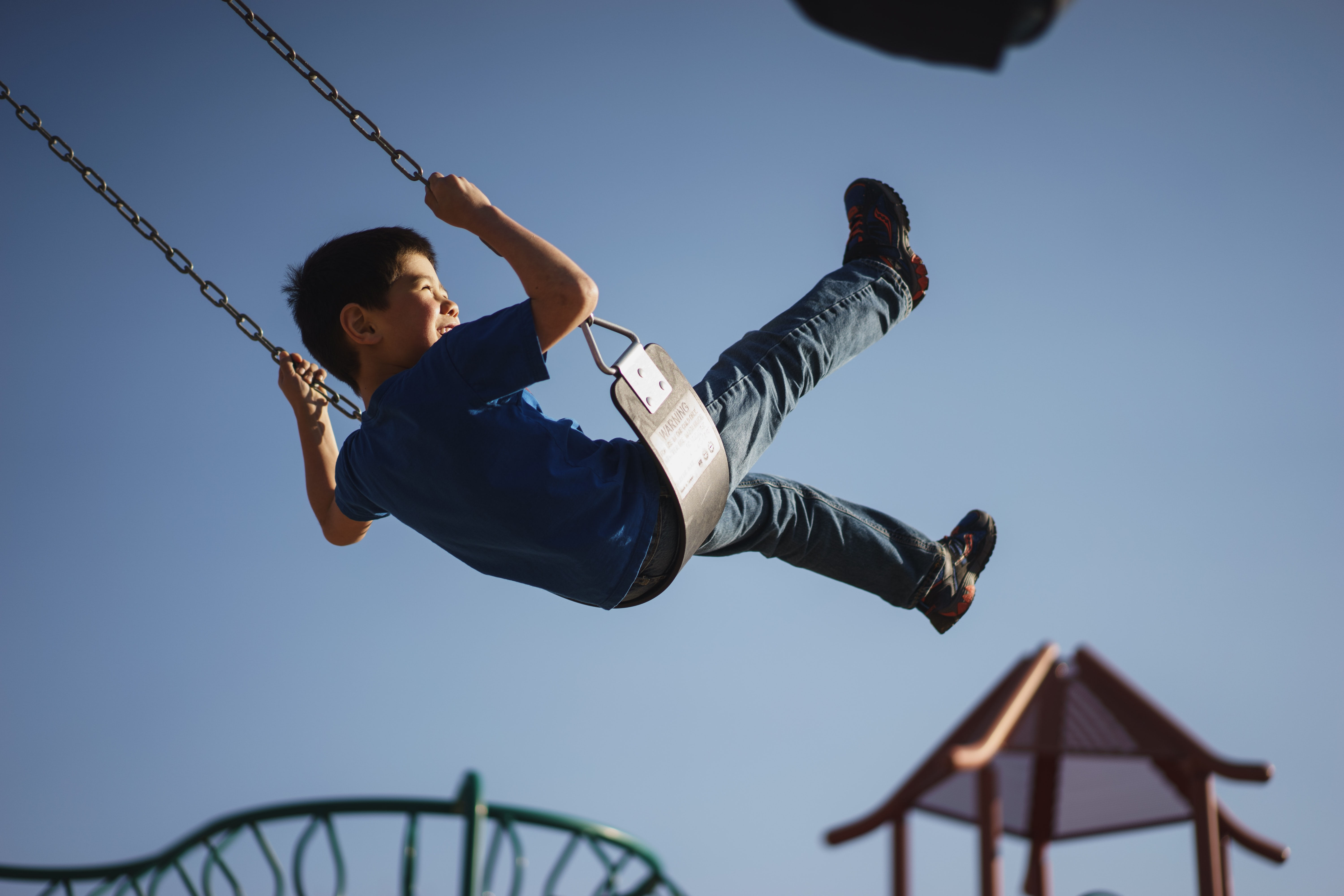 boy sitting on swing chair