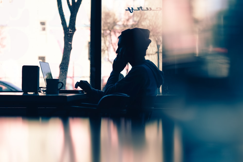 silhouette of a person sitting in front of a laptop