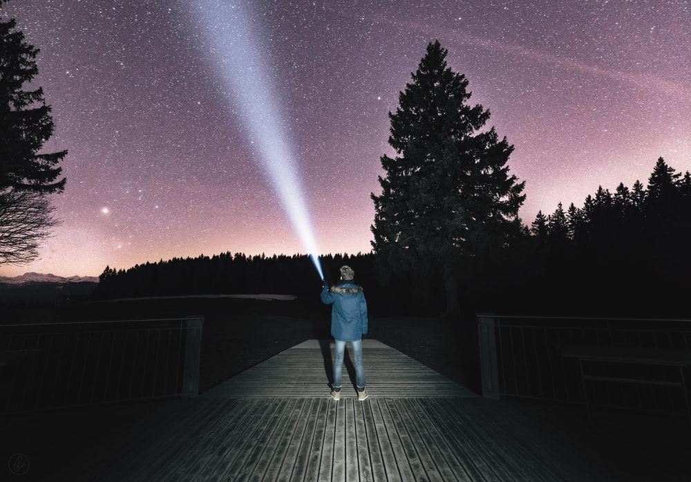 person holding flashlight aiming on sky