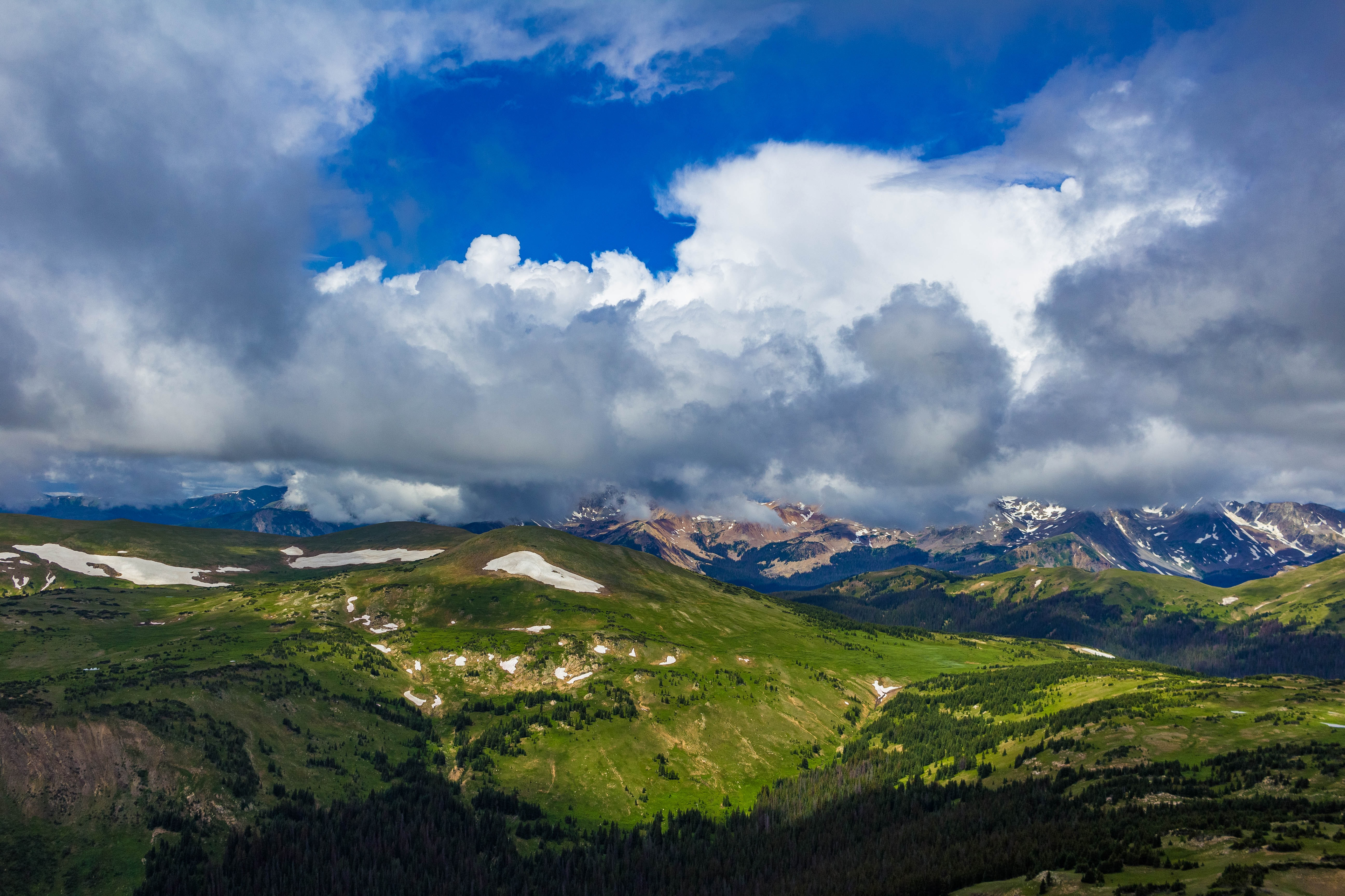 Clear sky with big fluffy clouds covering a lush green mountain with snow patches on Trail Ridge Road Summit.