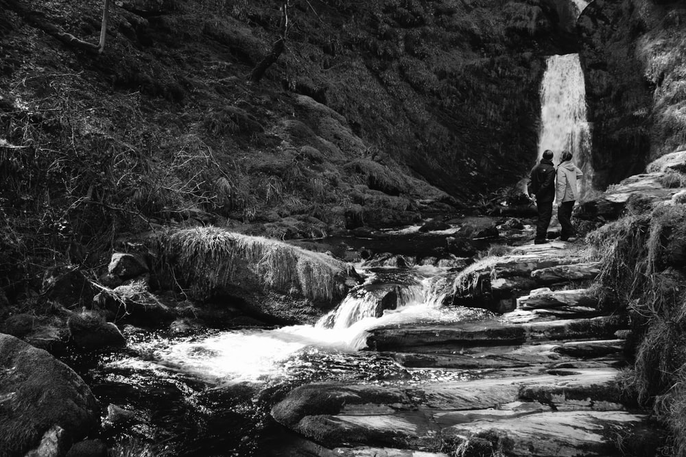 two persons standing near waterfalls