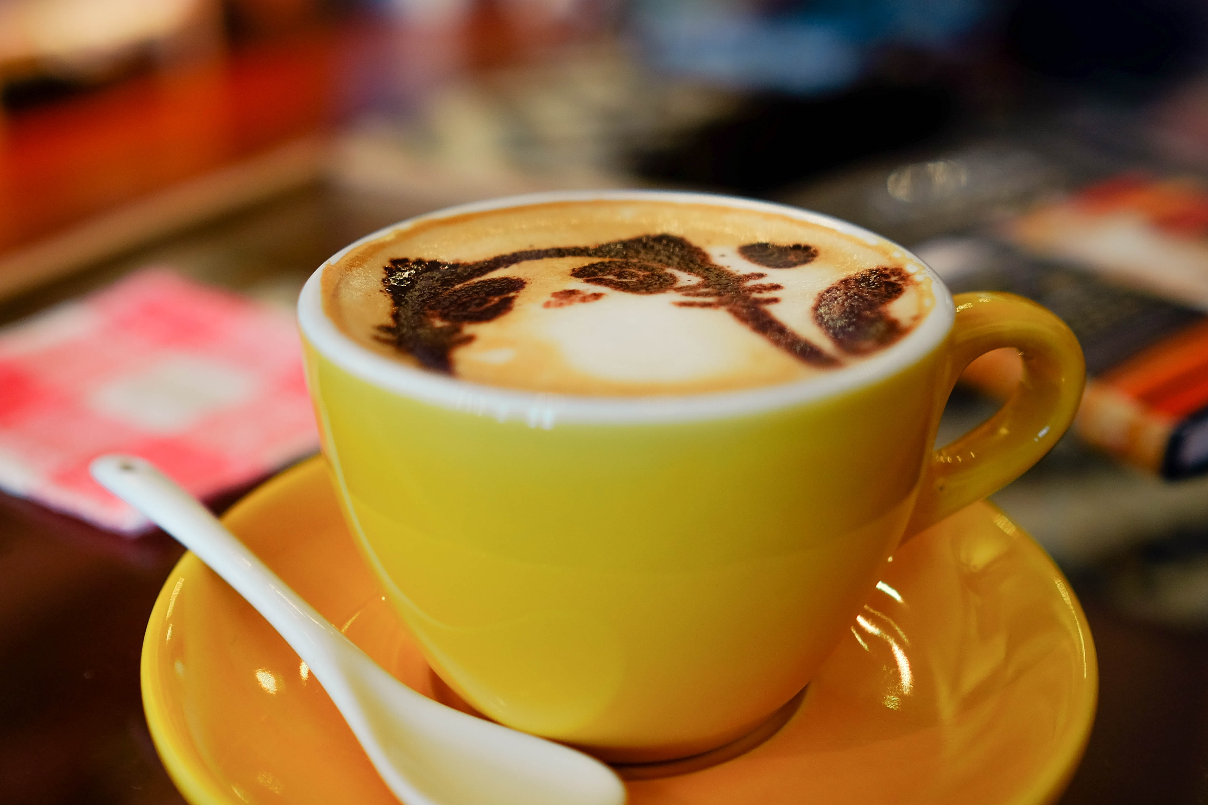 Small cappuccino in a yellow mug on a yellow saucer with a spoon and cat-shaped foam art