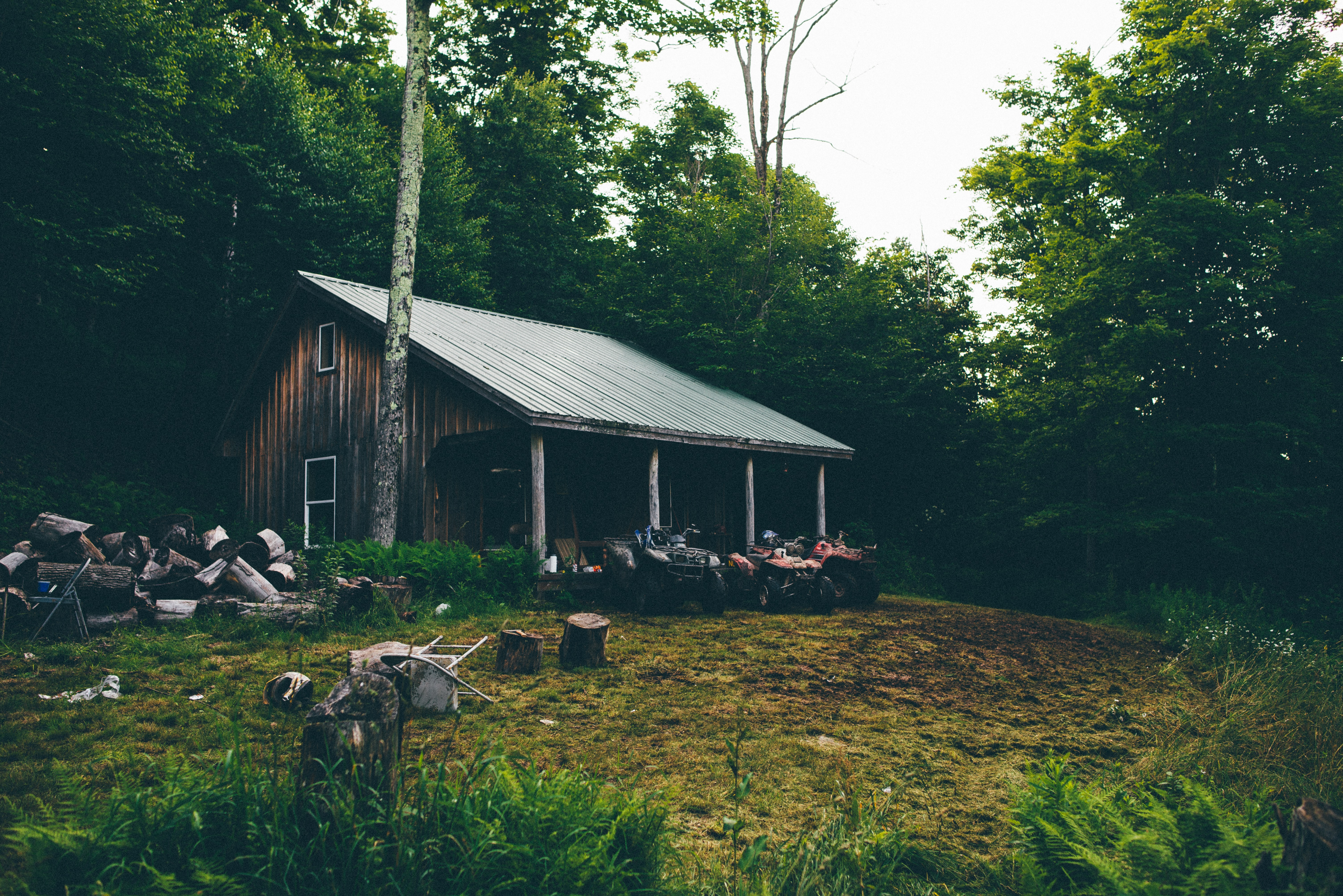Old cabin in the woods with a tin roof and three four wheelers, lawn chairs, and chopped wood in the yard