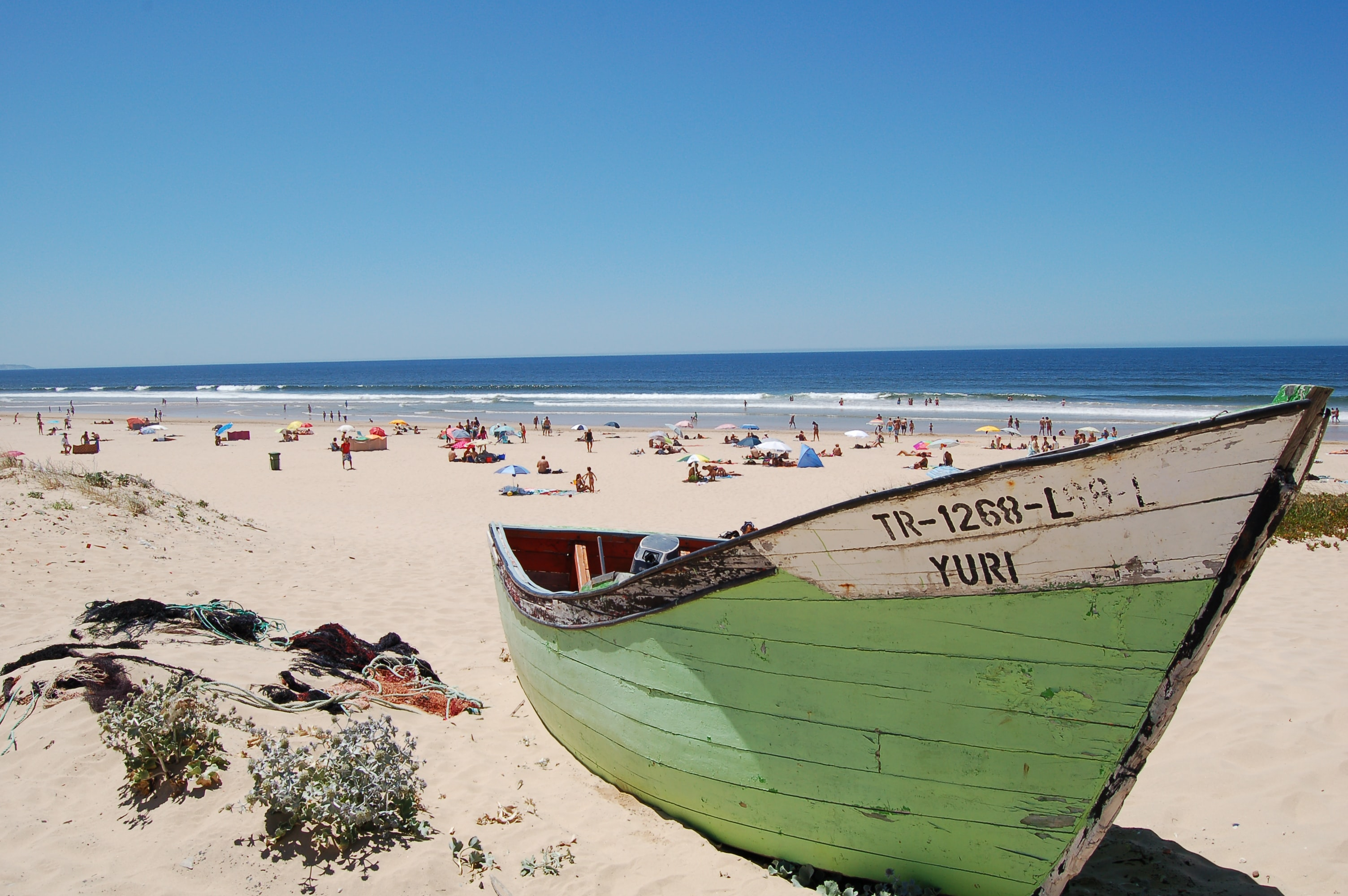 Exciting scenes at Lisbon beach featuring boat and the sunshine all over the shore