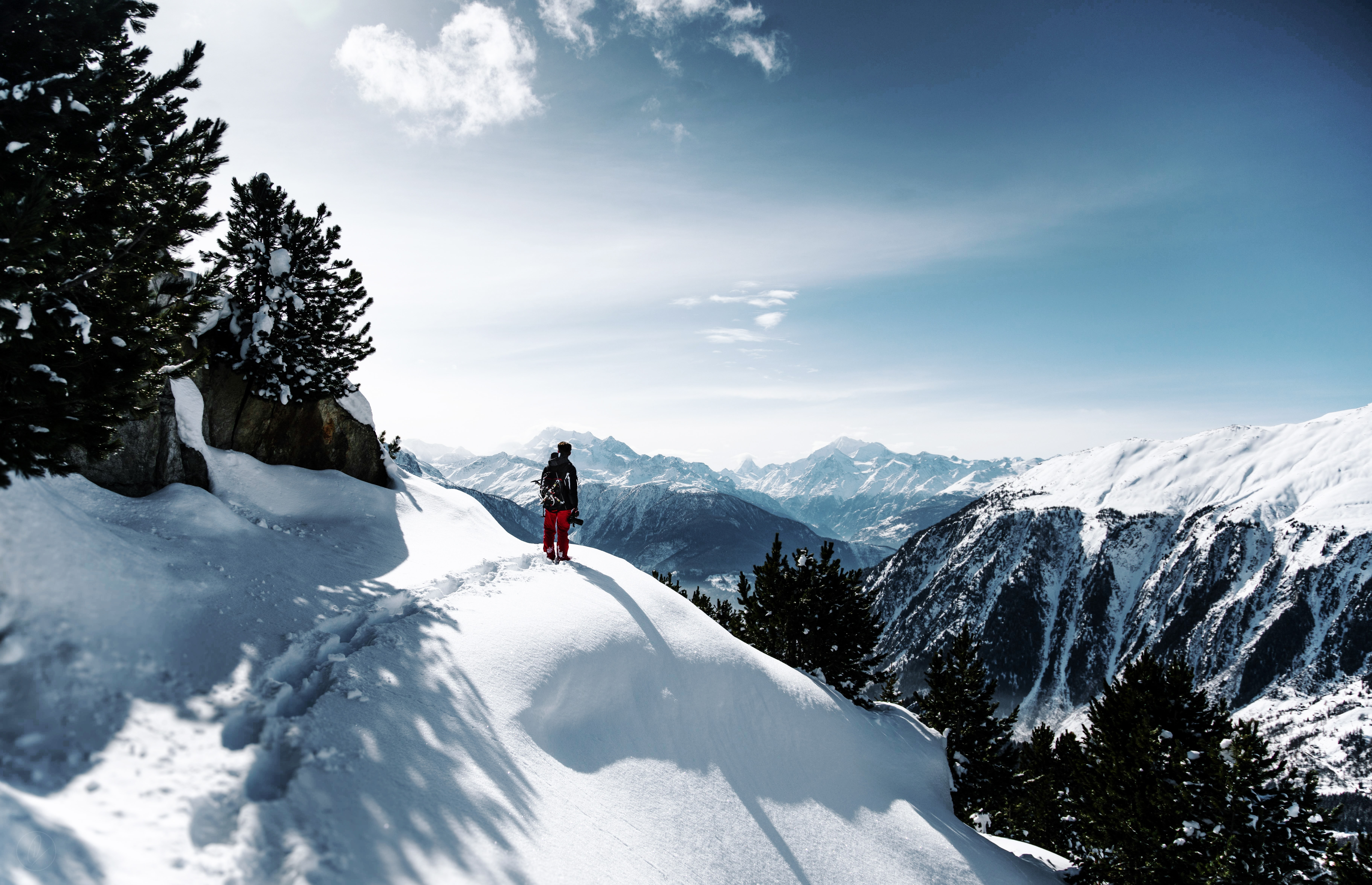 A hiker looks out onto snowy mountains
