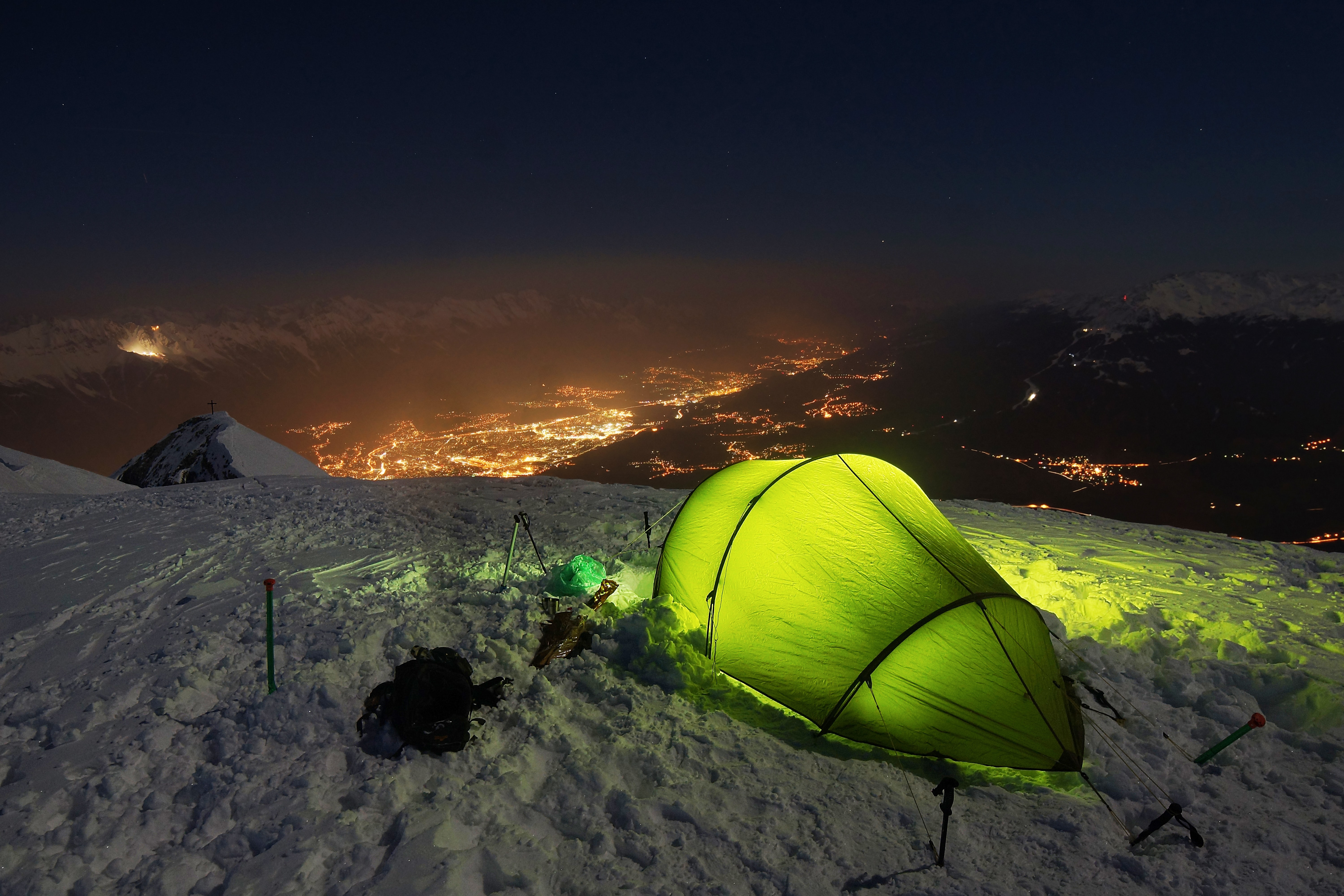 A green tent with green lights inside on top of a snow covered mountain overlooking the city lights.