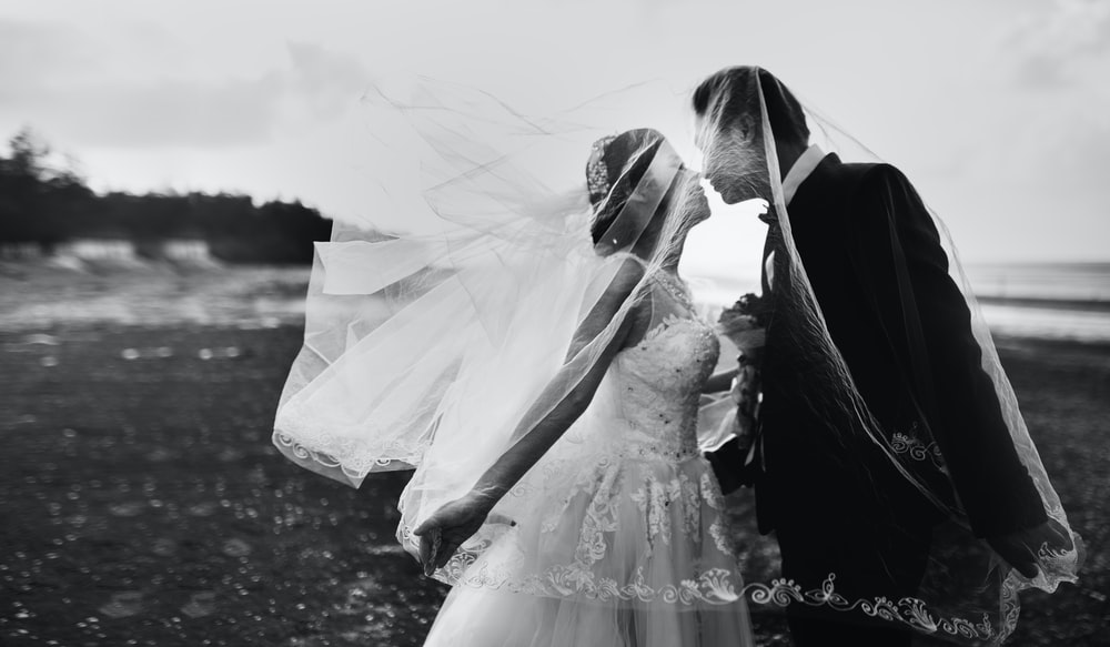 Black And White Photo Of A Bride S Veil Flying Up Over Her New Husband As They