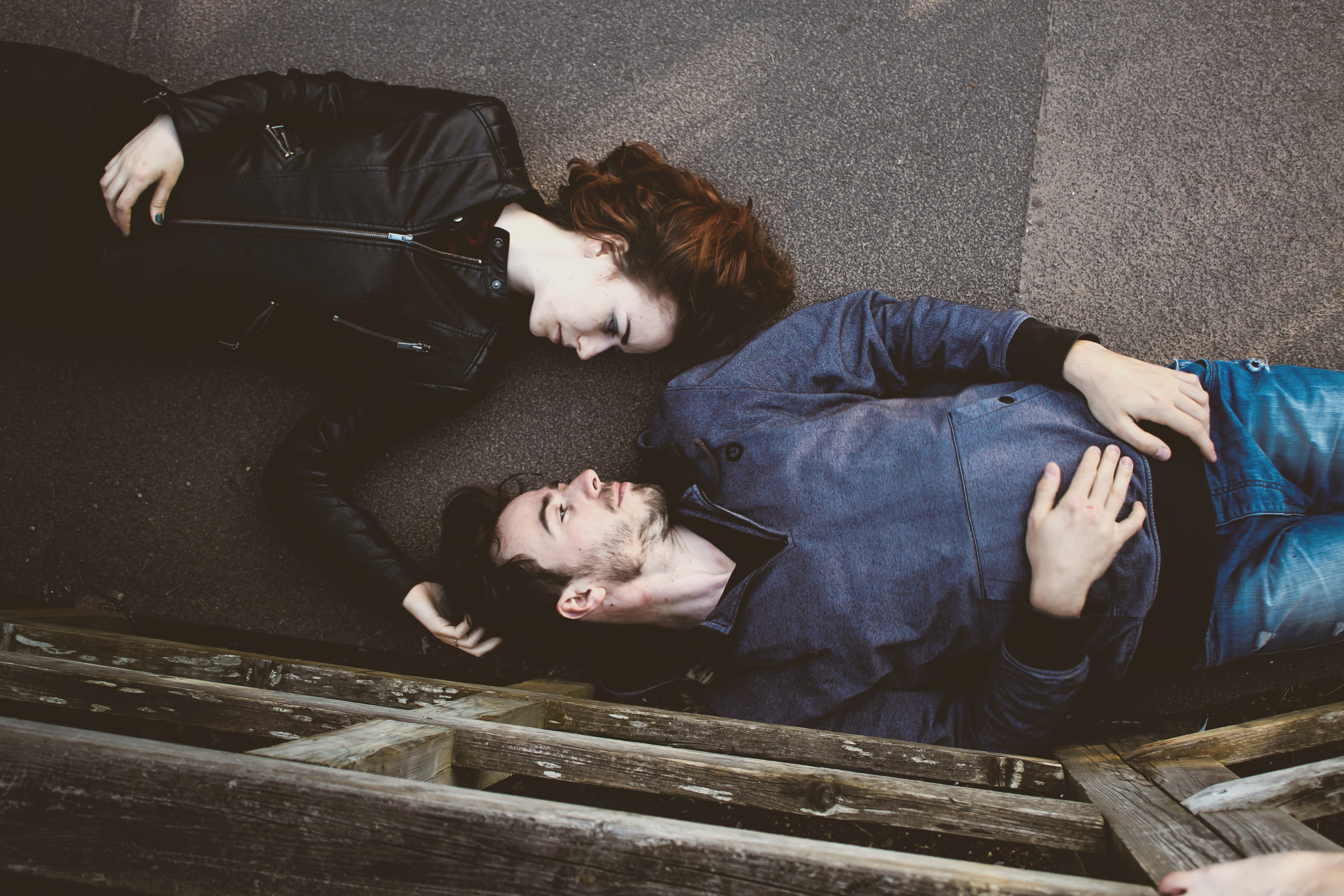 man and woman lying on gray concrete surface looking at each other
