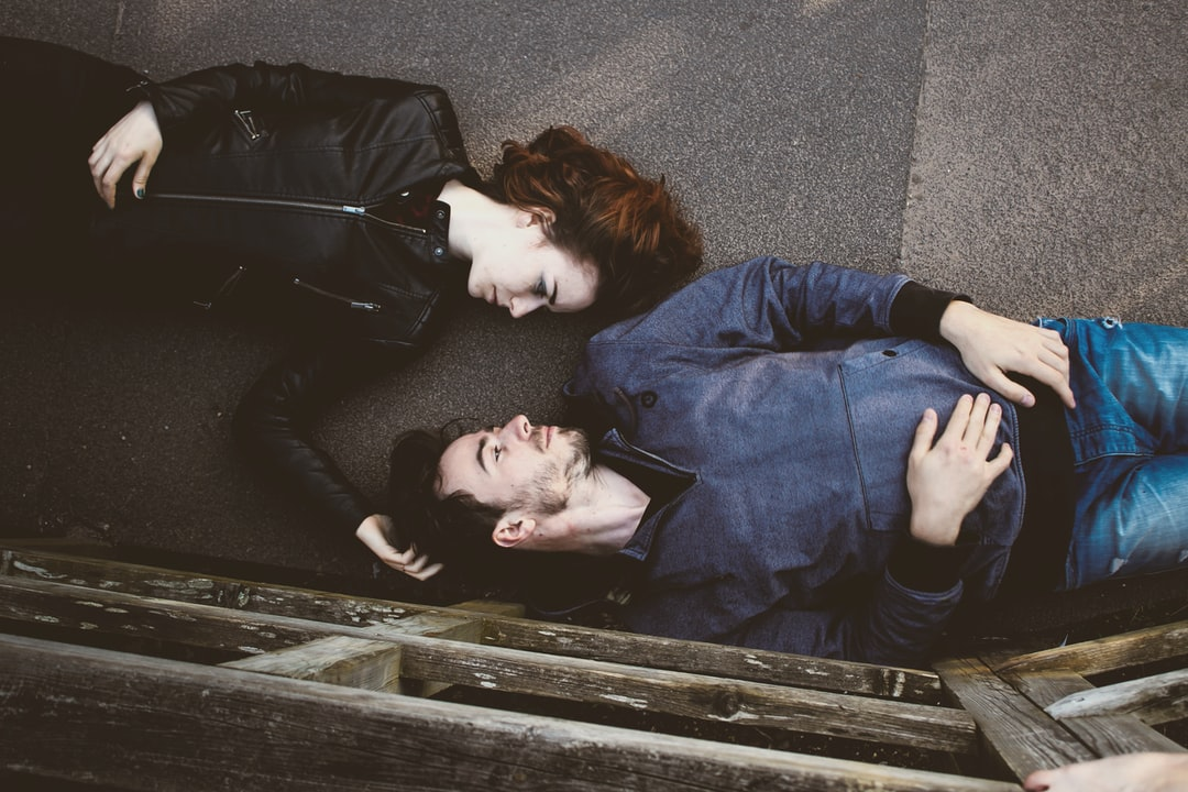 Overhead shot of man and woman laying on backs on walkway outdoors