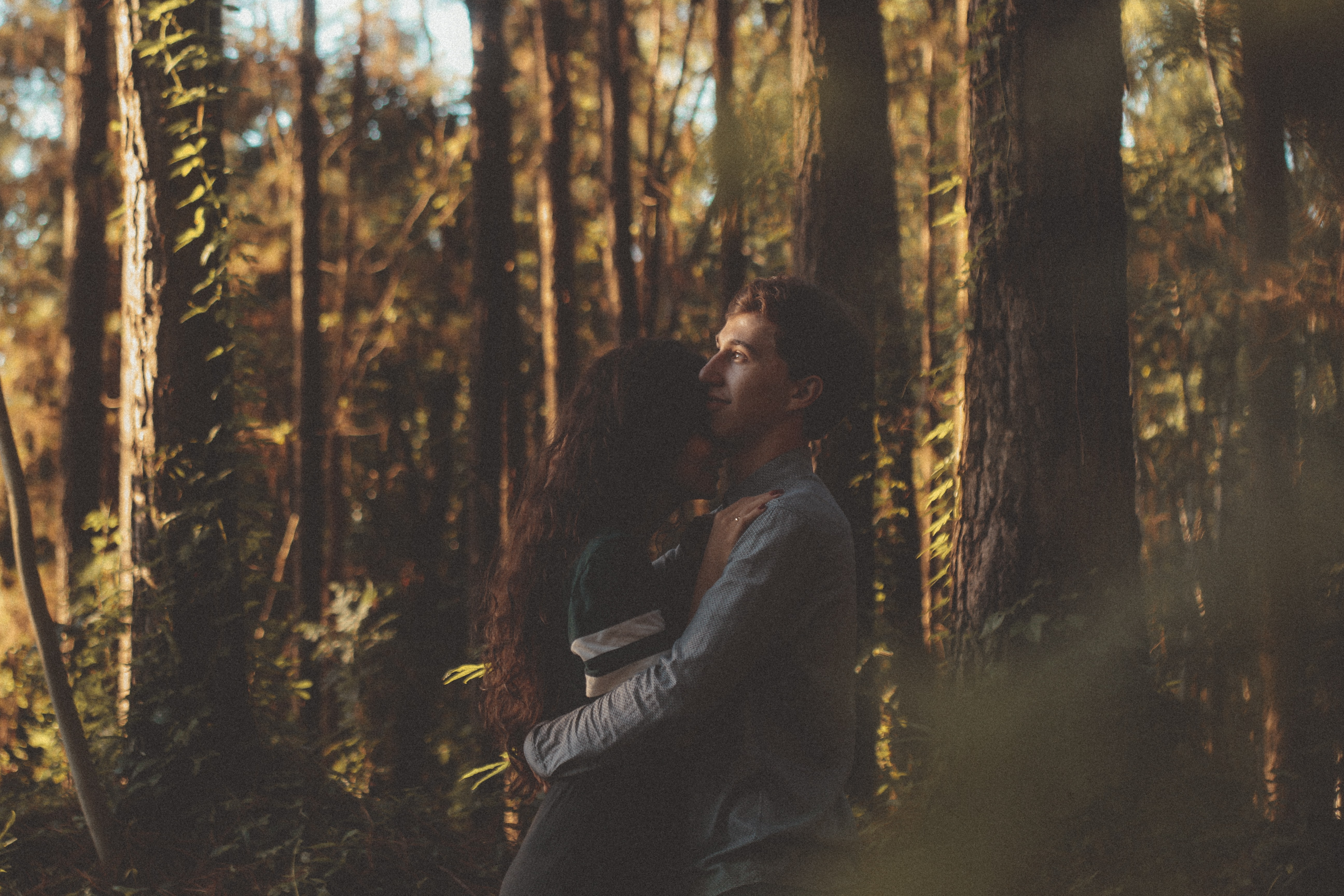 man and woman hugging each other on forest