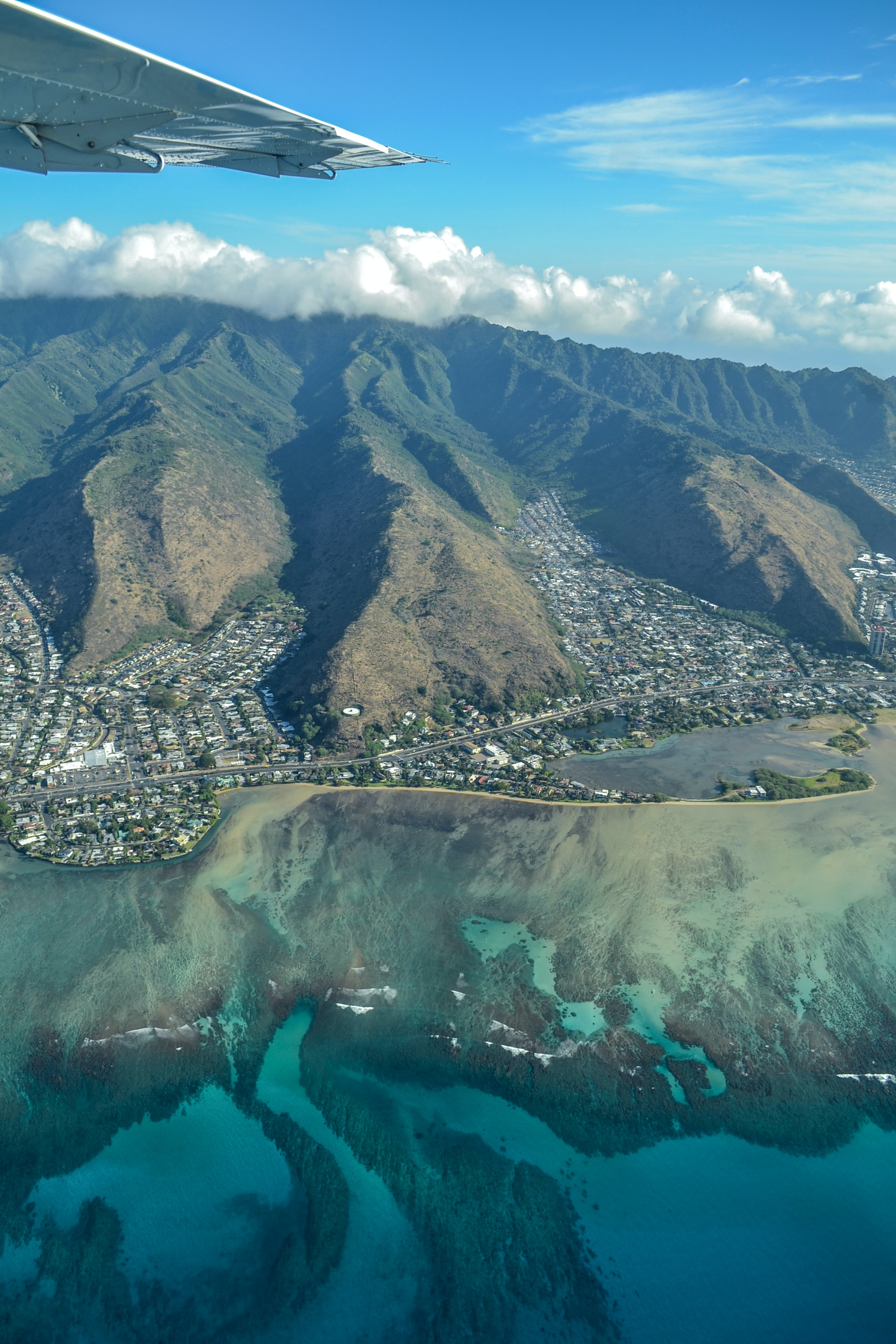 Aerial view of a mountain town along the coast from a plane in O'ahu