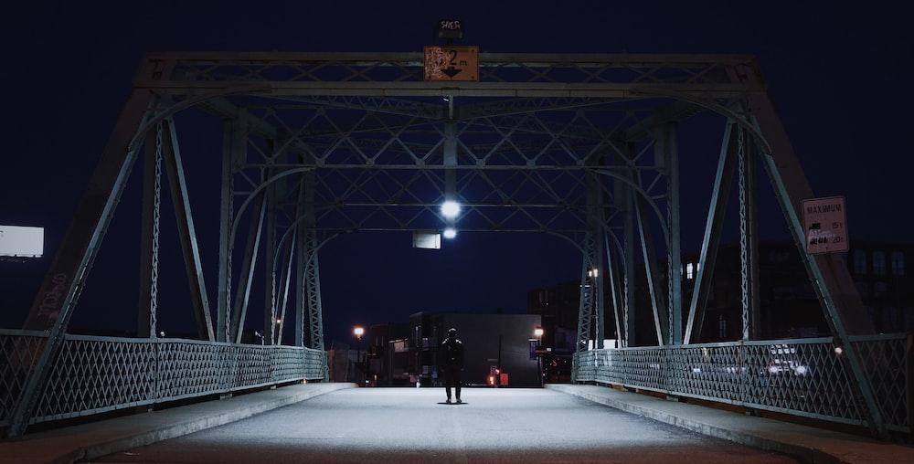 silhouette of man on bridge