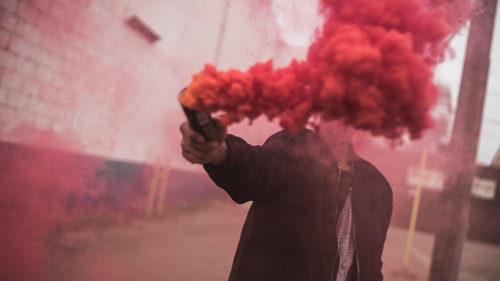man holding red smoke grenade