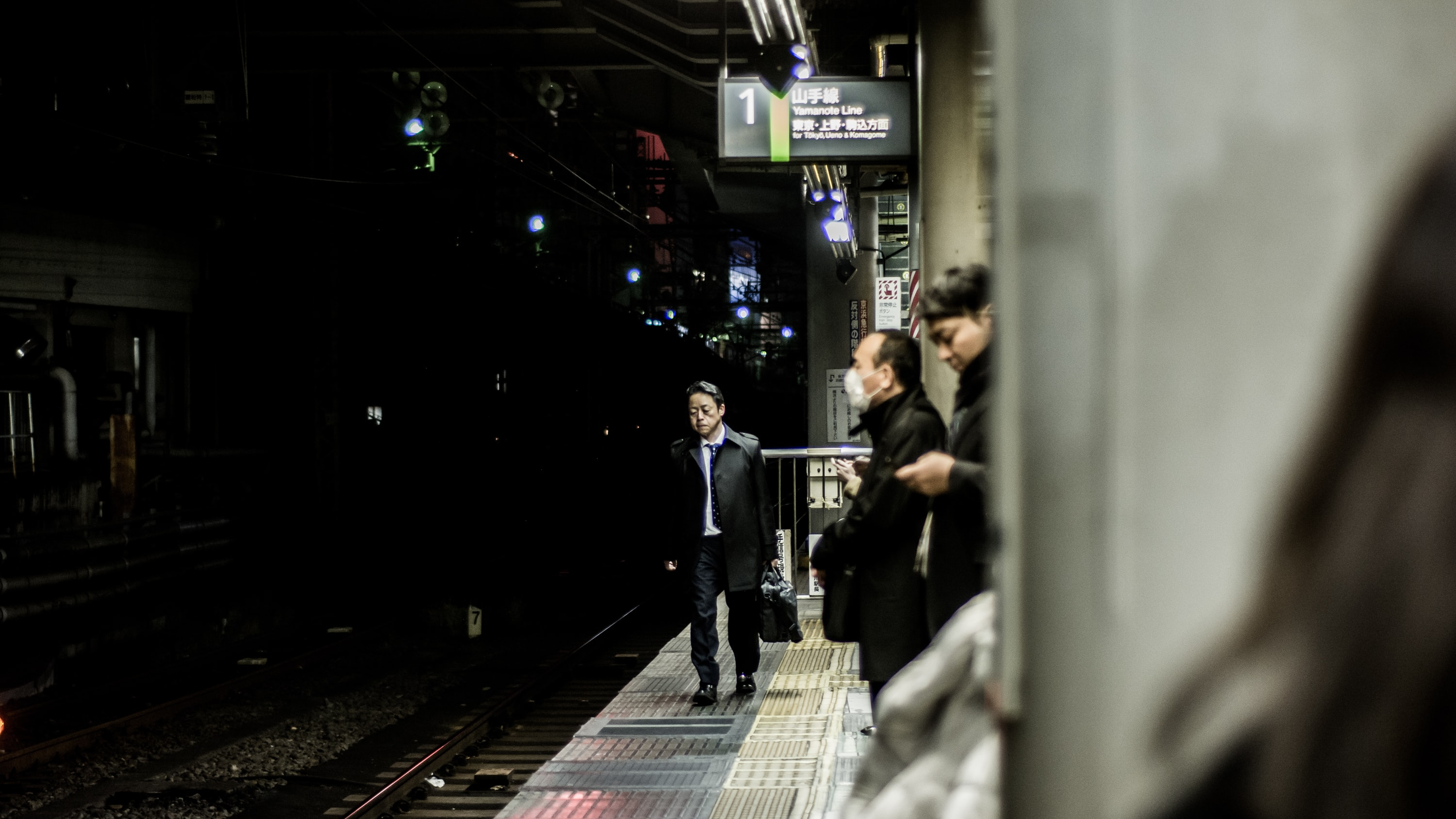 Commuters are walking and waiting by the railway platform of Shinjuku Station.