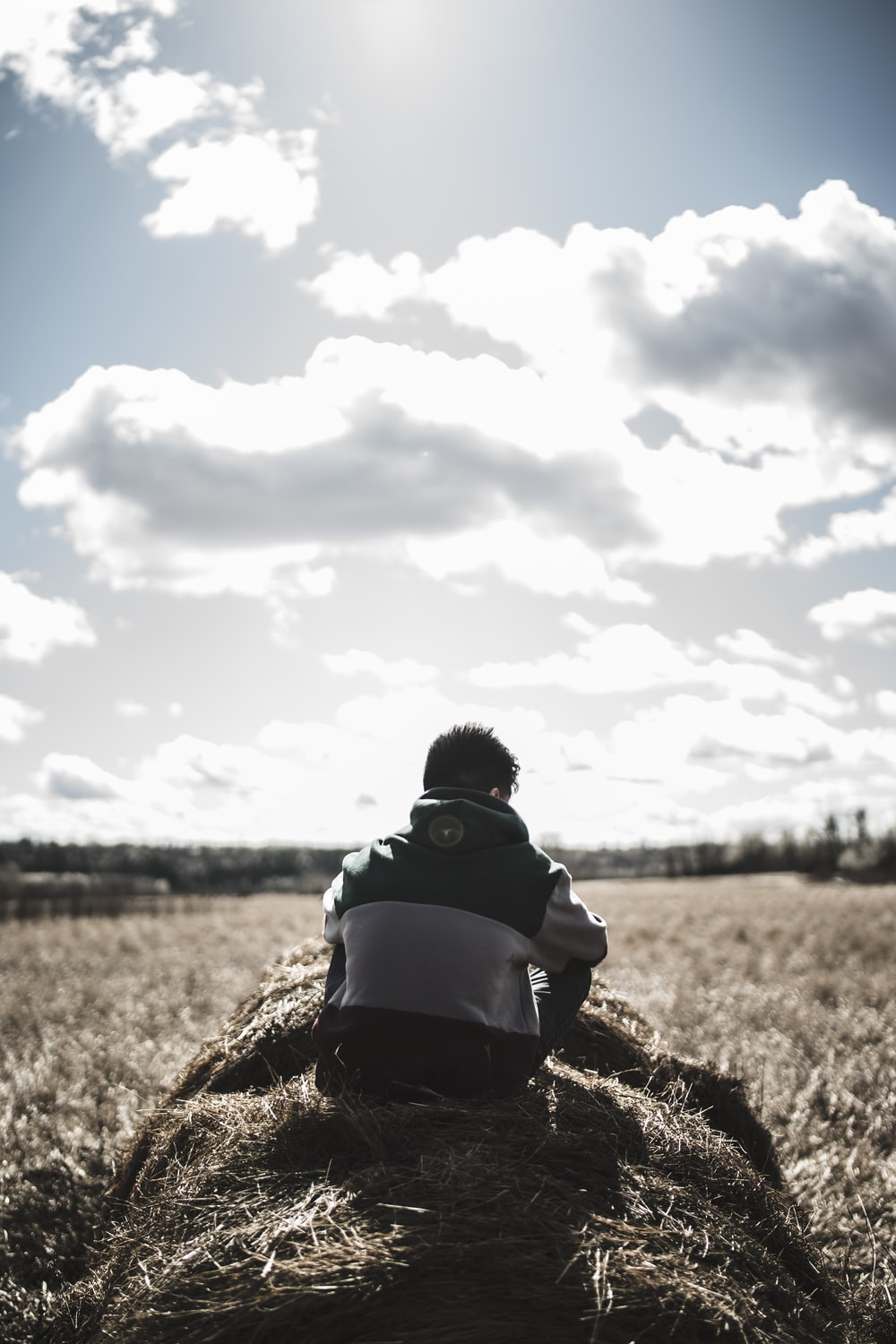 grayscale photography of man siting on hay grass