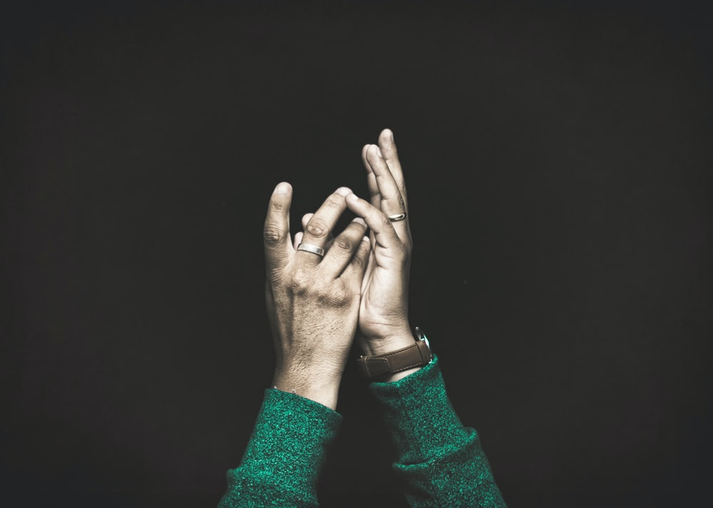 closeup photo of person raising both arms