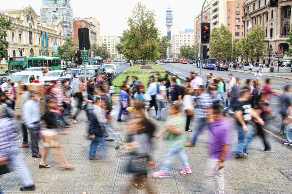 timelapse photo of people passing the street