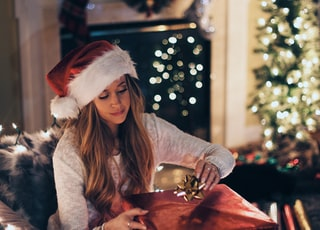 woman putting ribbon in red gift box near lighted Christmas tree inside room