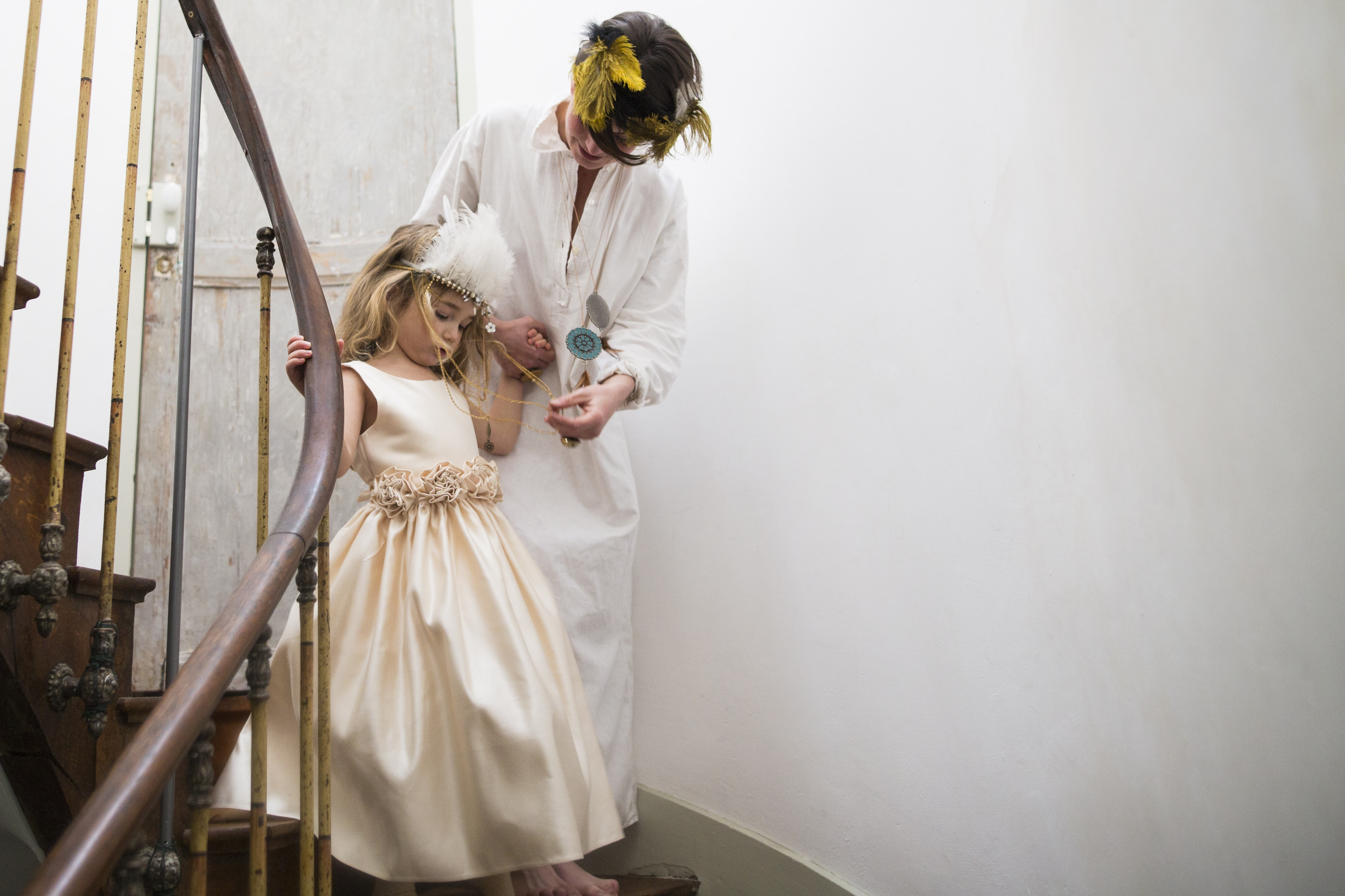 Mother and daughter dressed elegantly in white descending a turn in a staircase.