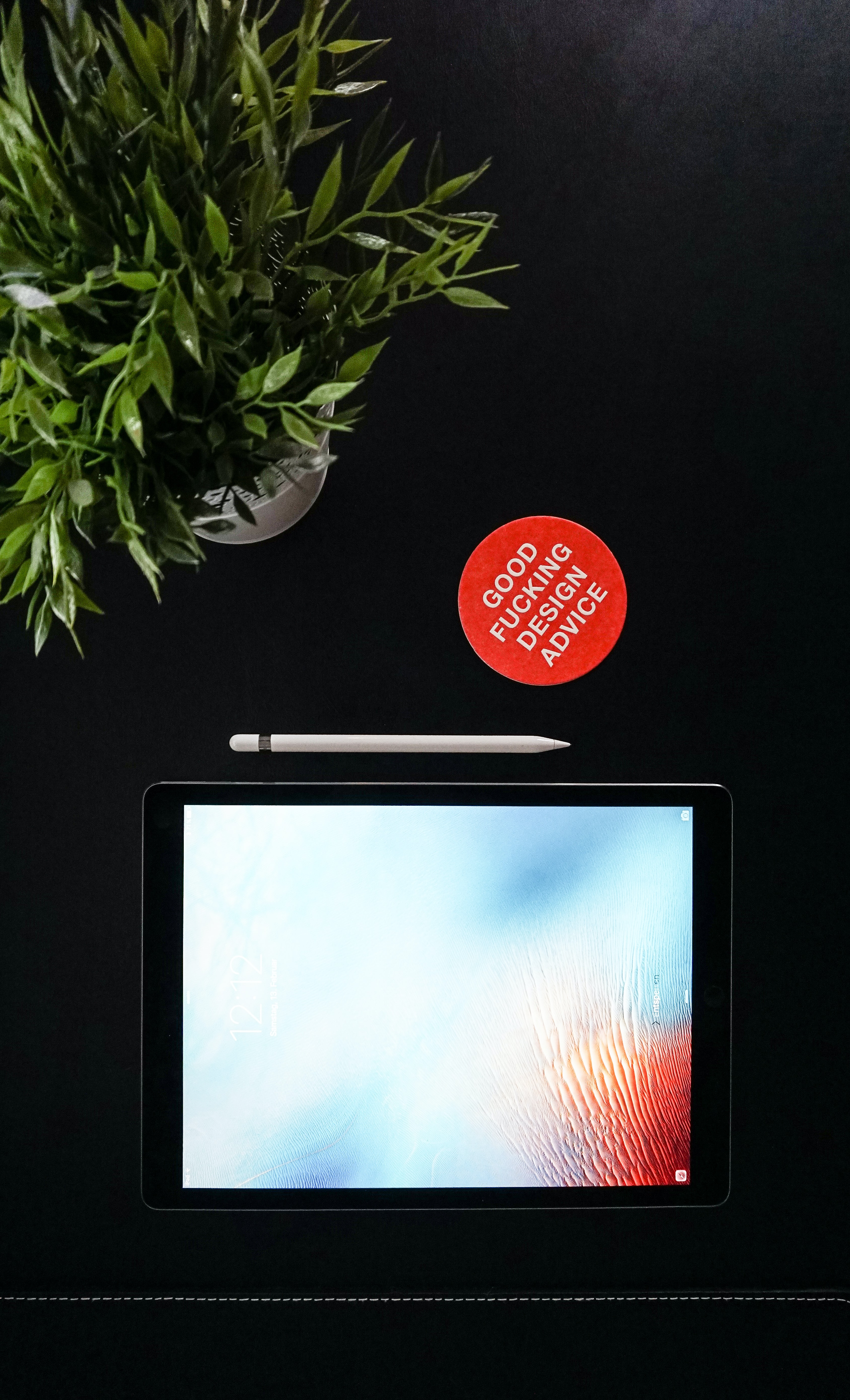 Tablet with blank display and stylus next to plant and design text in red circle