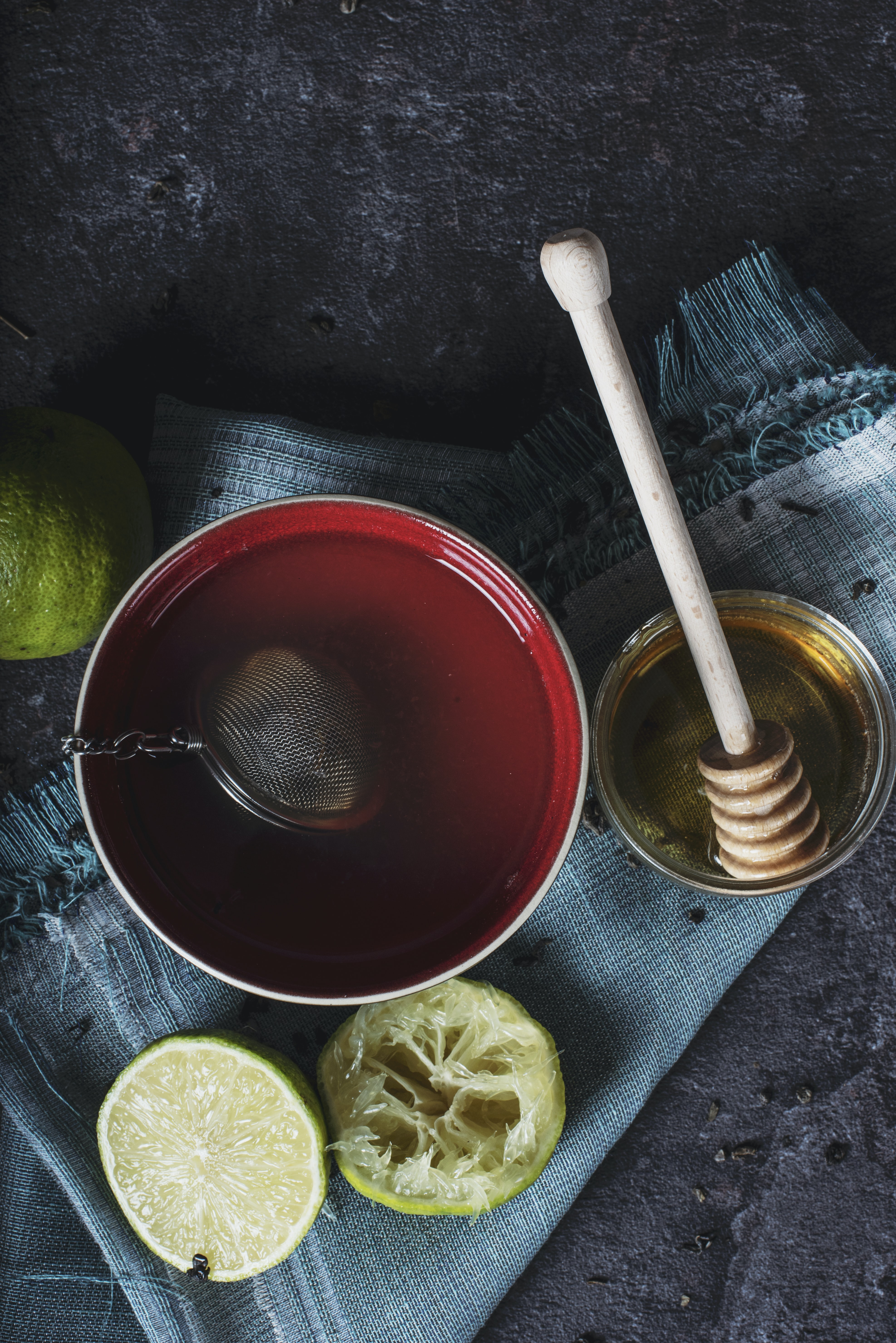 red ceramic bowl filled with water beside lime and honey