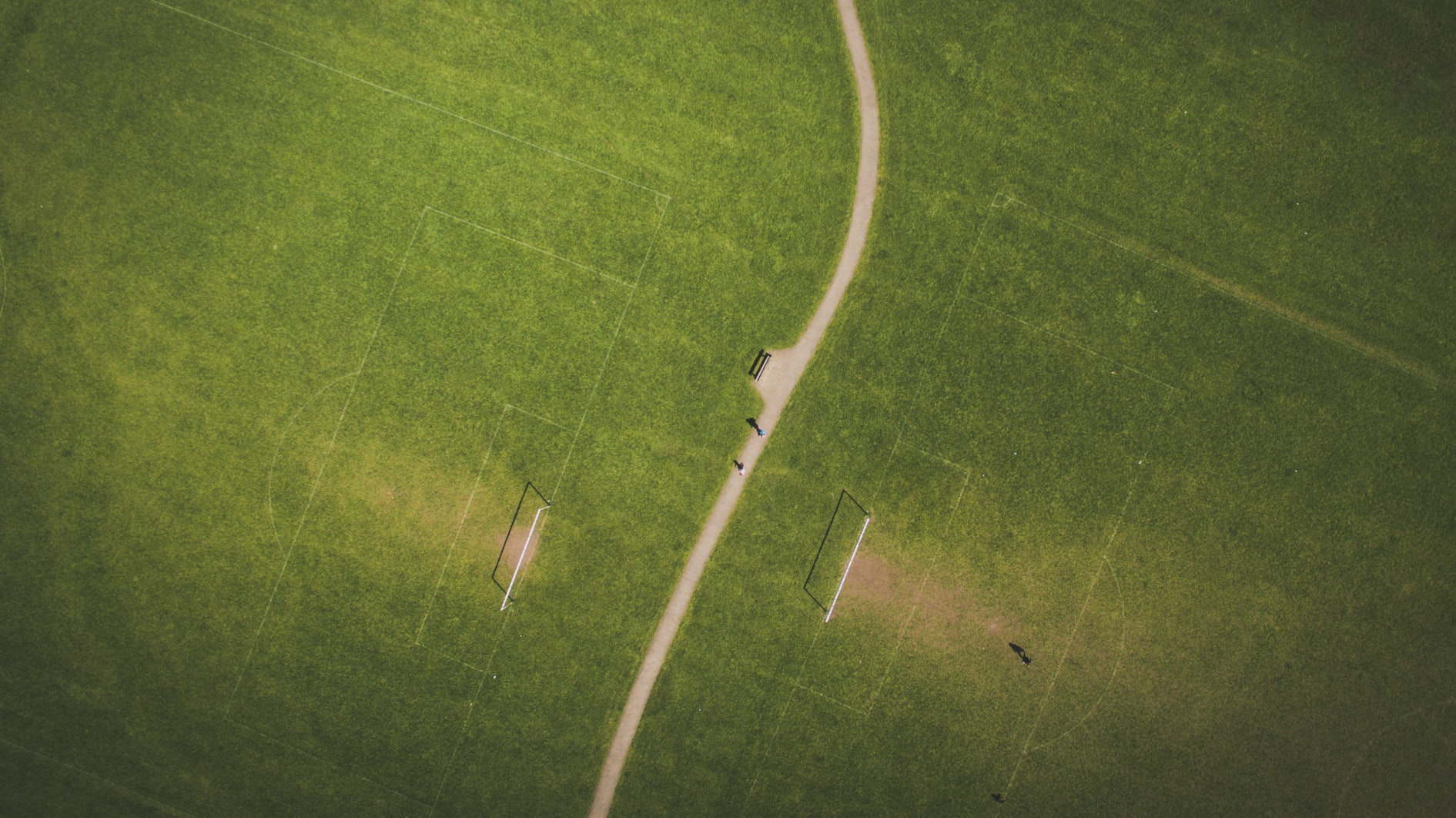 A drone shot of a narrow path with green football fields with goalposts on both sides