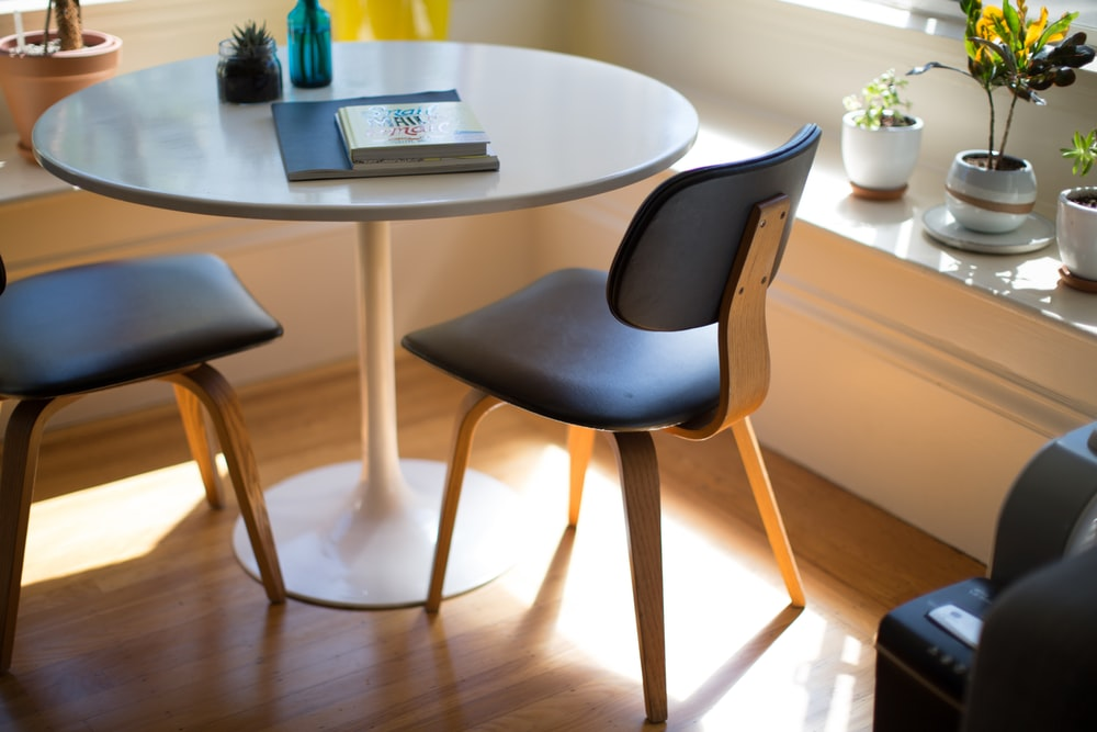 round white dining table beside two chairs on brown hardwood flooring