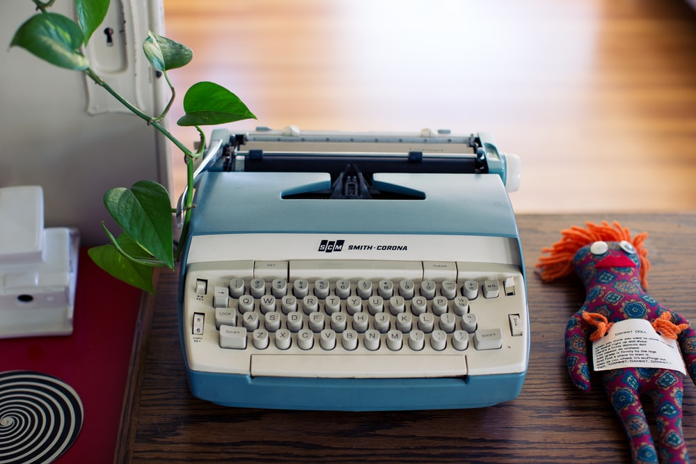white and beige typewriter and red and black Voodoo doll