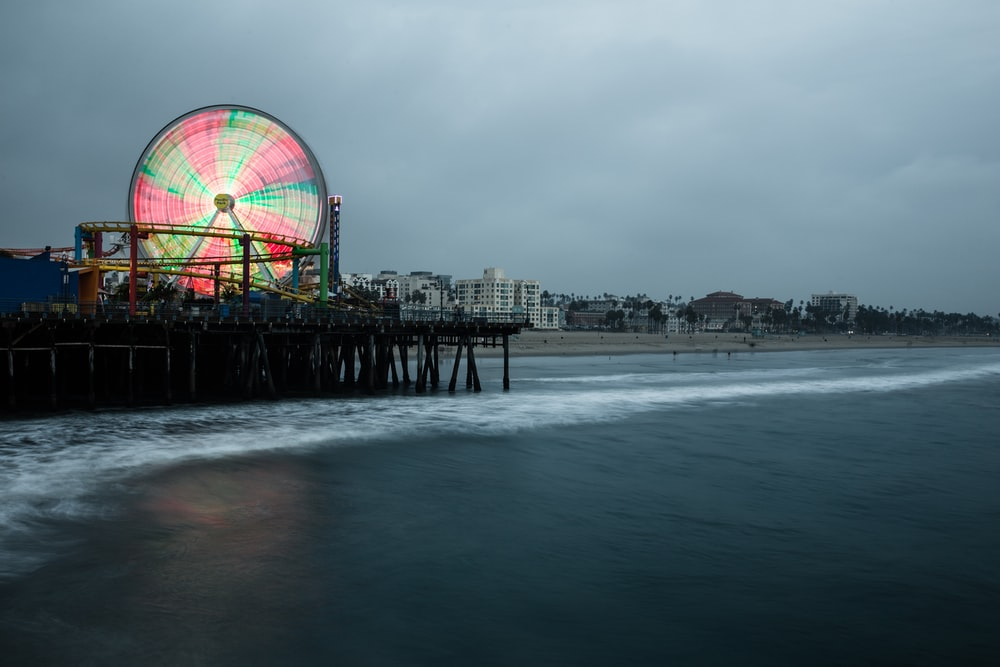 lighted Ferris wheel in the city near body of water