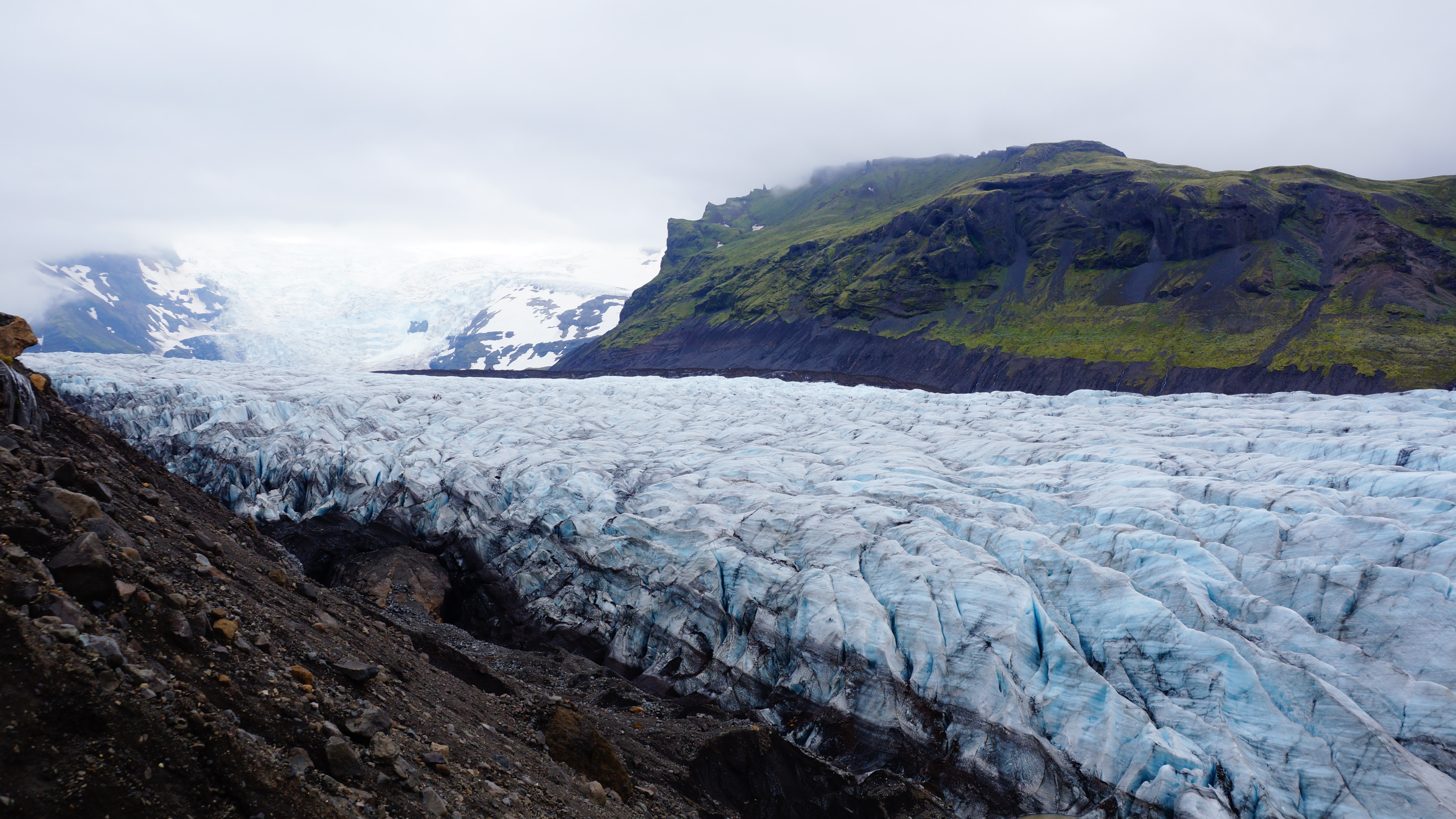 An undulating glacier near moss-covered mountains